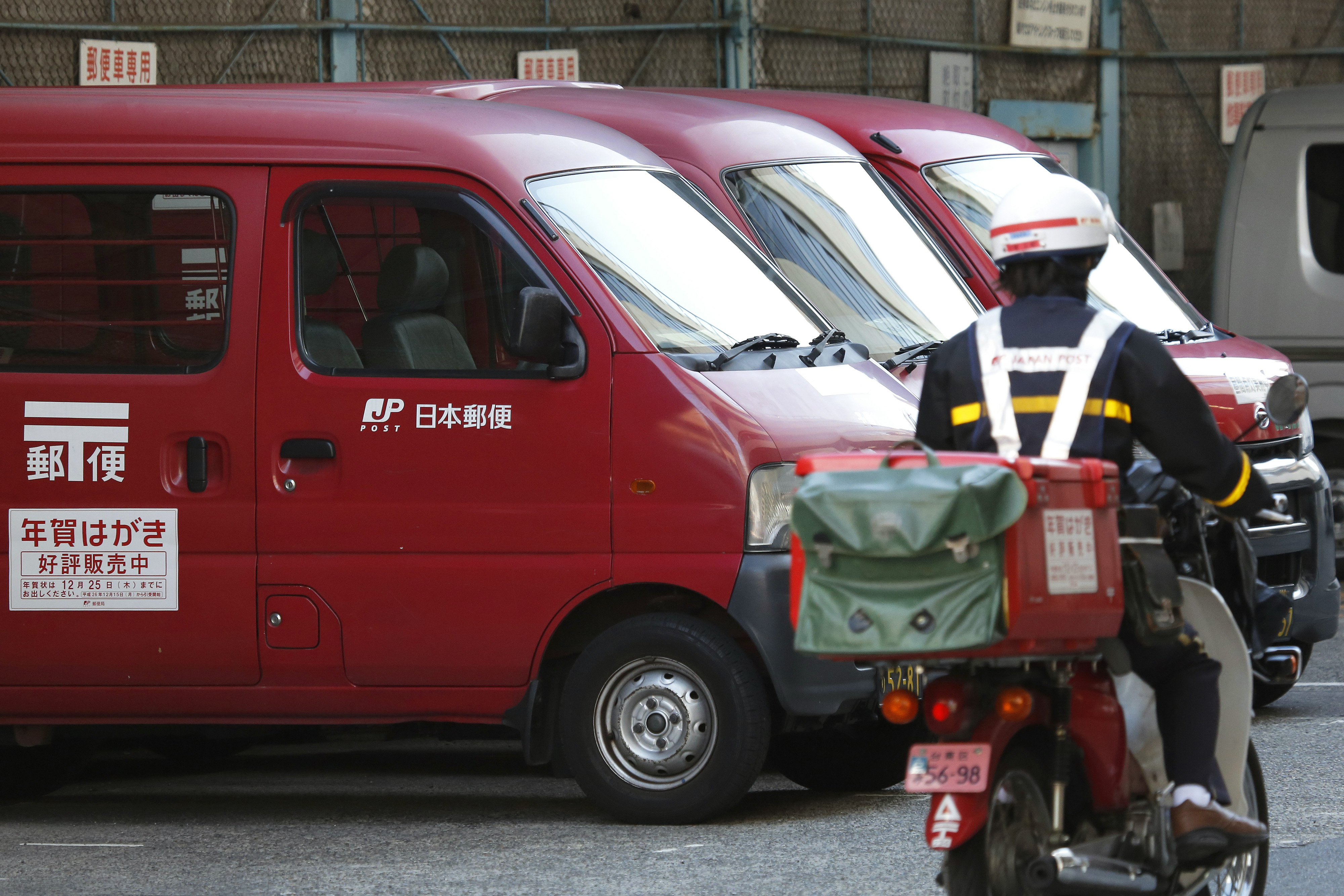 Japan Post vans sit parked while an employee drives a motorcycle into the company's branch in Tokyo, Japan