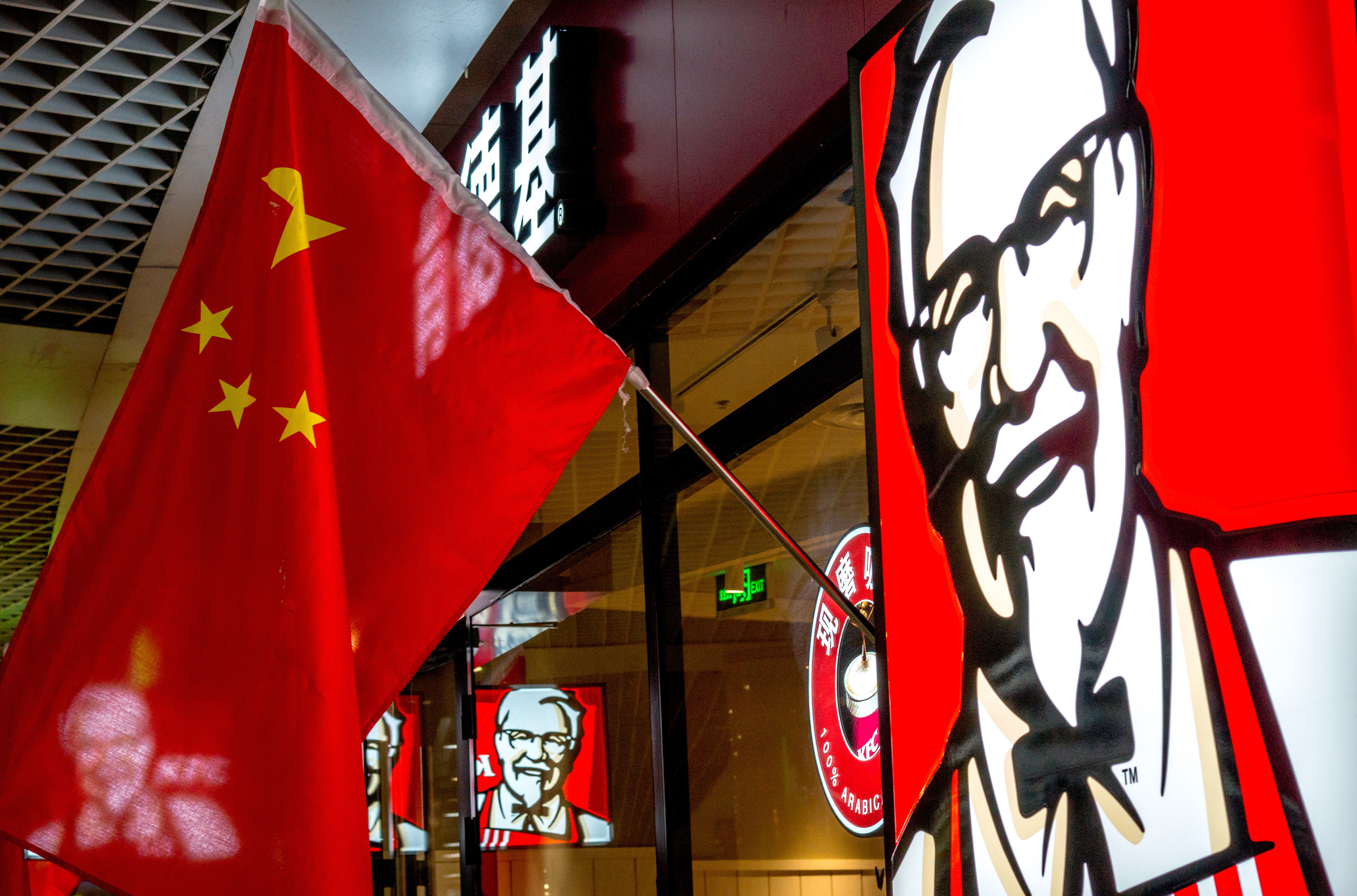 "TIANJIN, CHINA - 2015/02/21: A KFC restaurant hangs up China's national flags in lunar new year.  KFC restaurants in China will start selling freshly ground coffee in 2015 to become a lower-cost ""premium"" alternative to Starbucks. The initiative began earlier this year and is expected to perform in 2,500 KFCs in China by the end of this year. (Photo by Zhang Peng/LightRocket via Getty Images)"