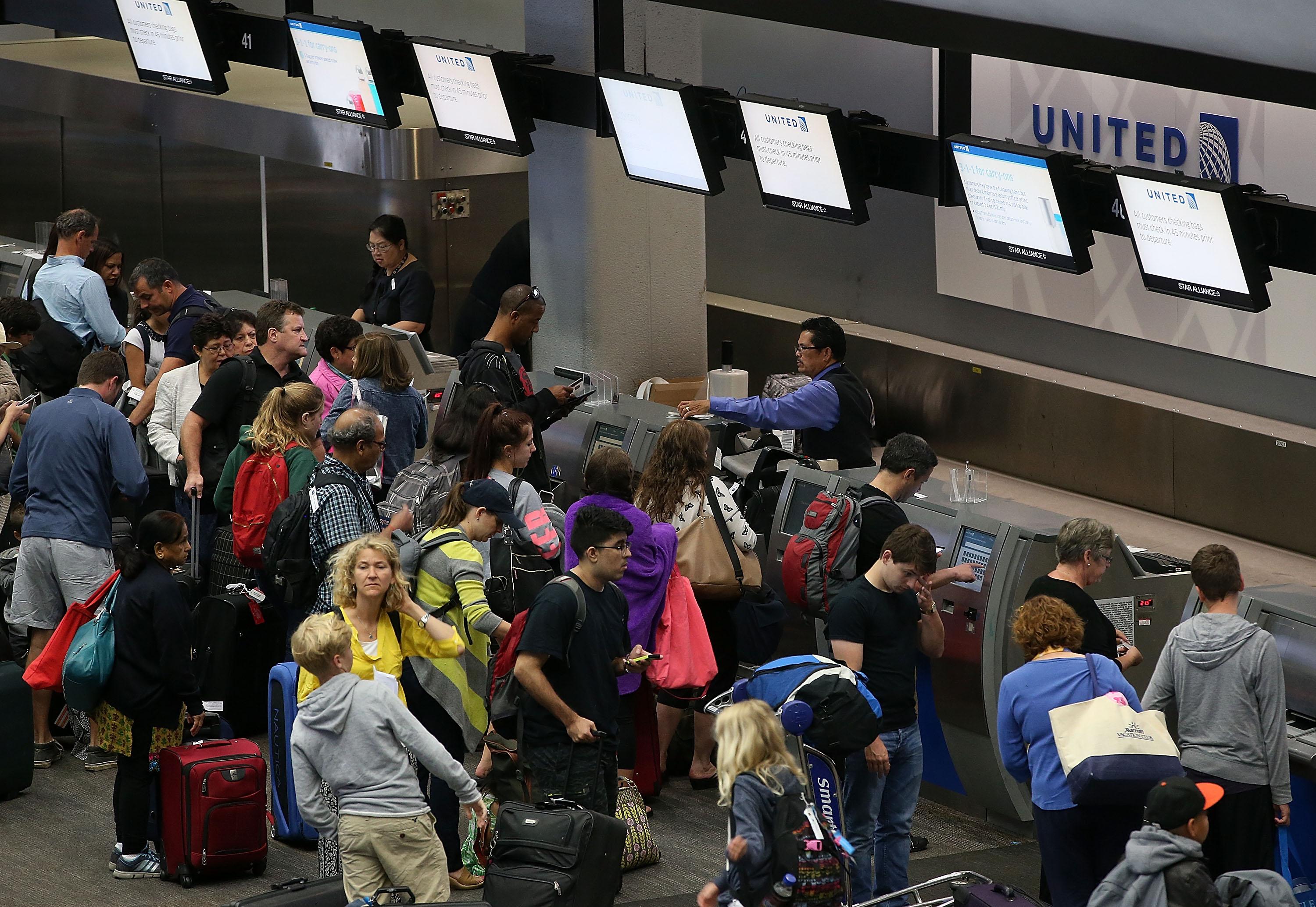 United Airlines passengers wait in line to check in for flights at San Francisco International Airport on July 8, 2015 in San Francisco, California.