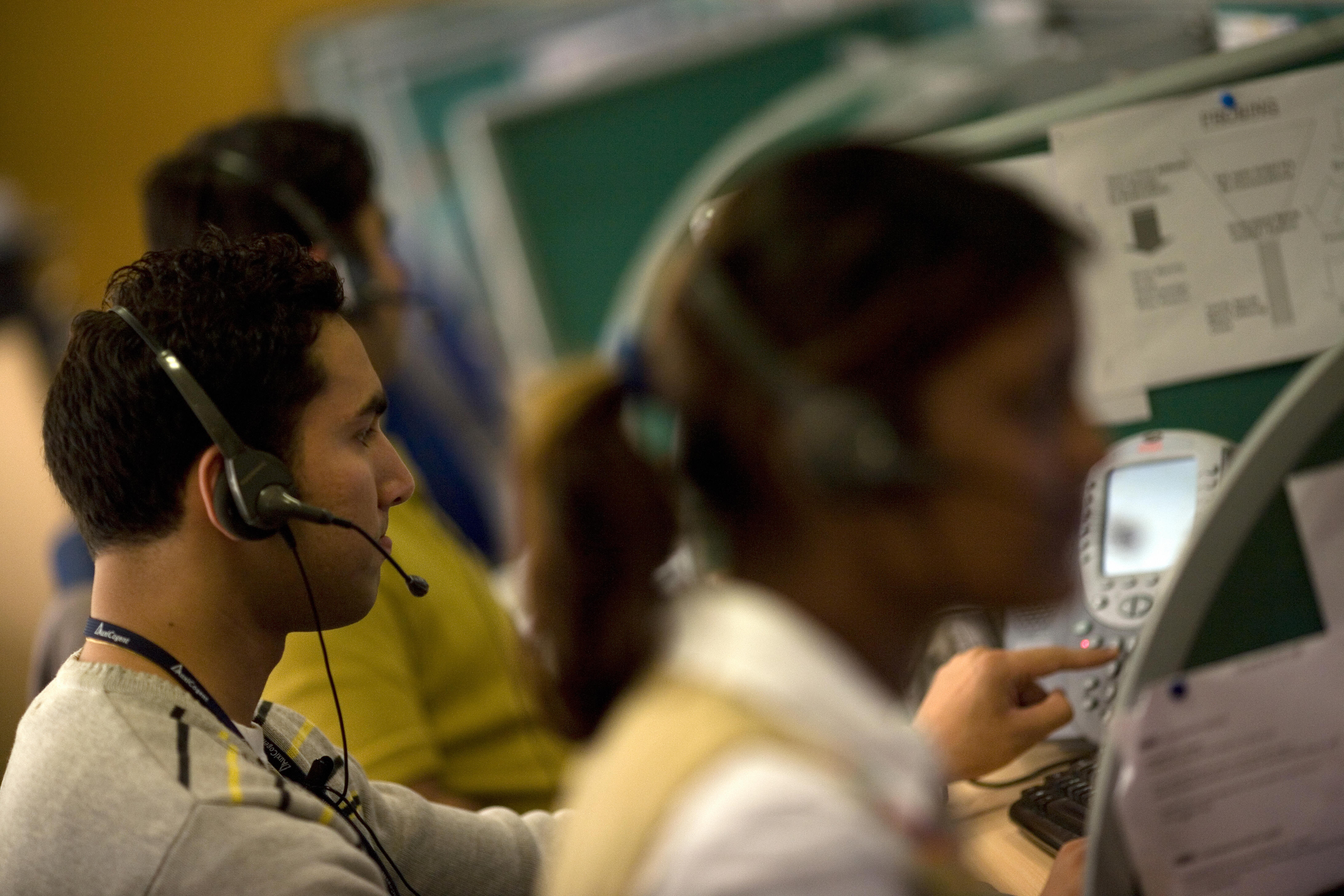 Indian workers answer telephone calls at