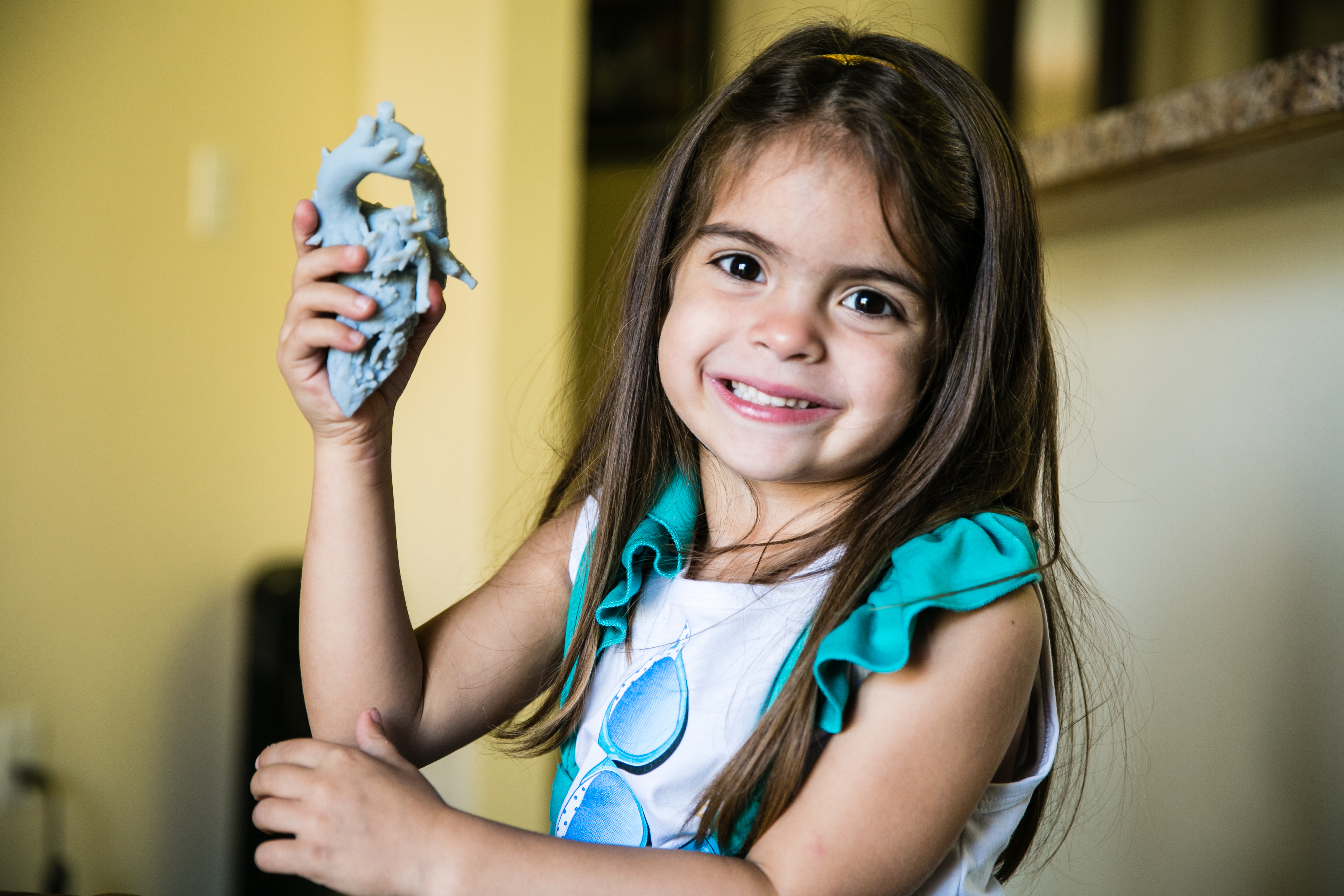Mia Gonzalez holding one of the 3D prints of her heart.