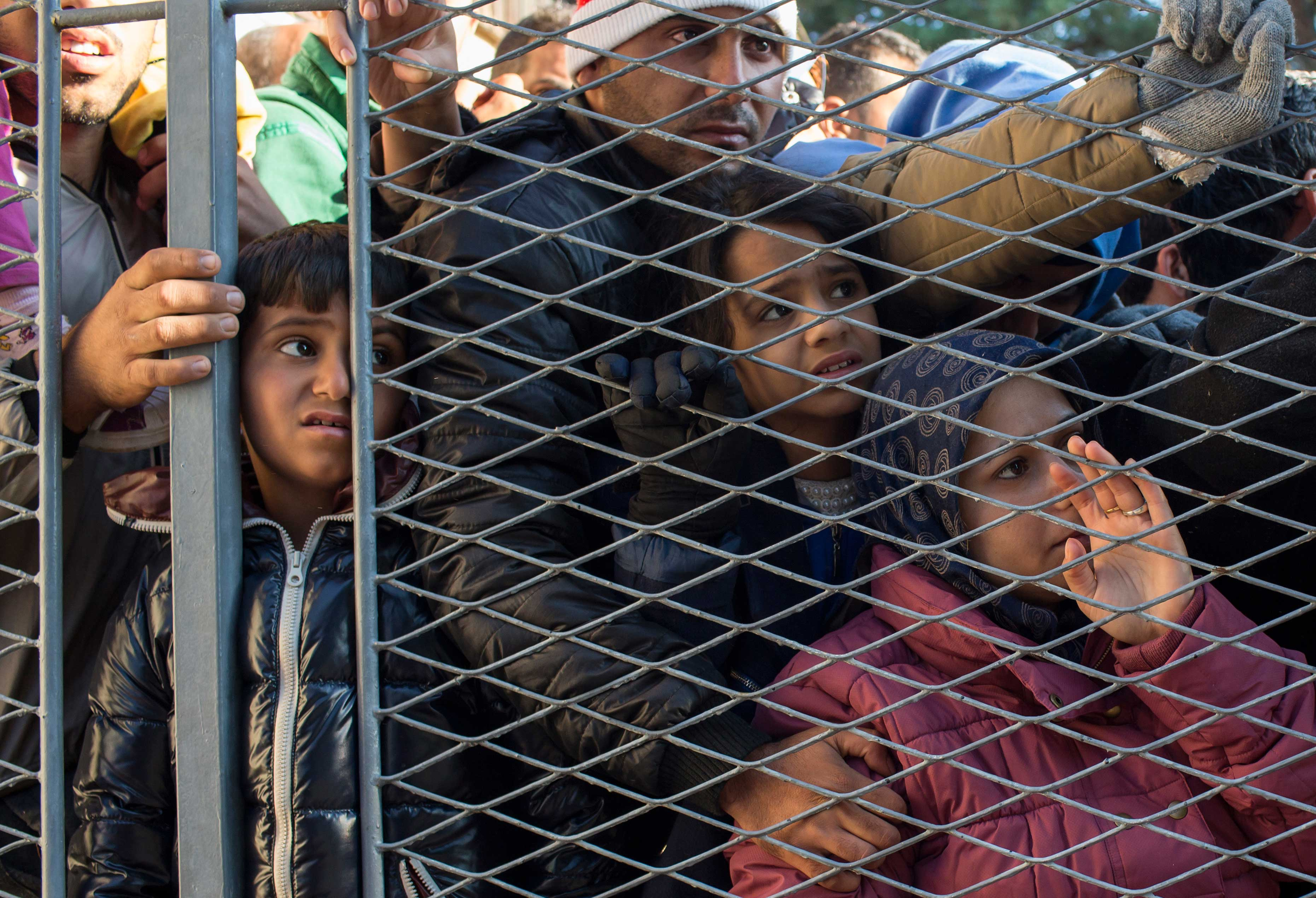 Migrants stand behind a gate as they wait to board buses inside a registration camp in Opatovac