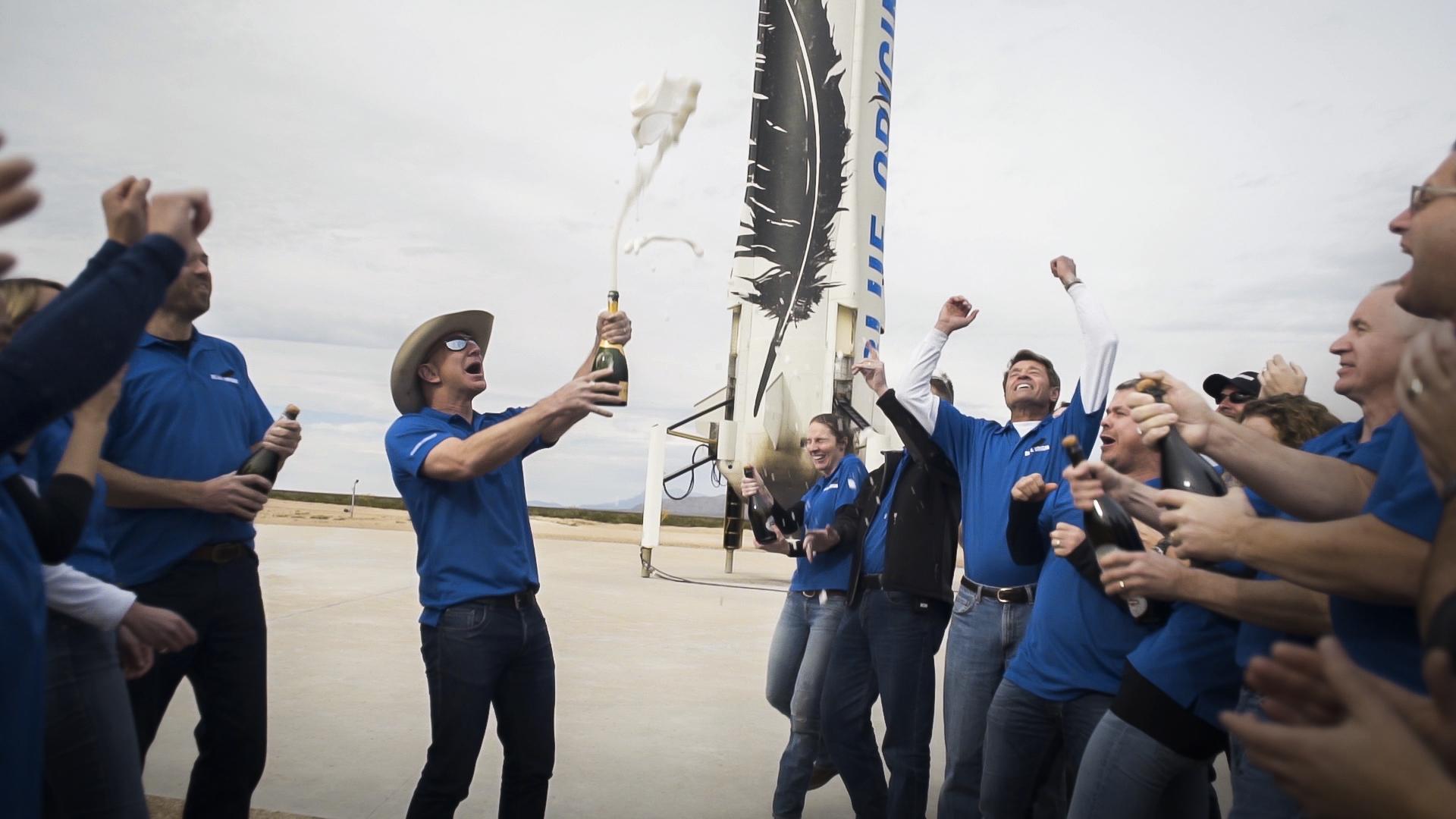 Jeff Bezos pops a bottle of champagne in celebration of a successful Blue Origin rocket launch and landing.