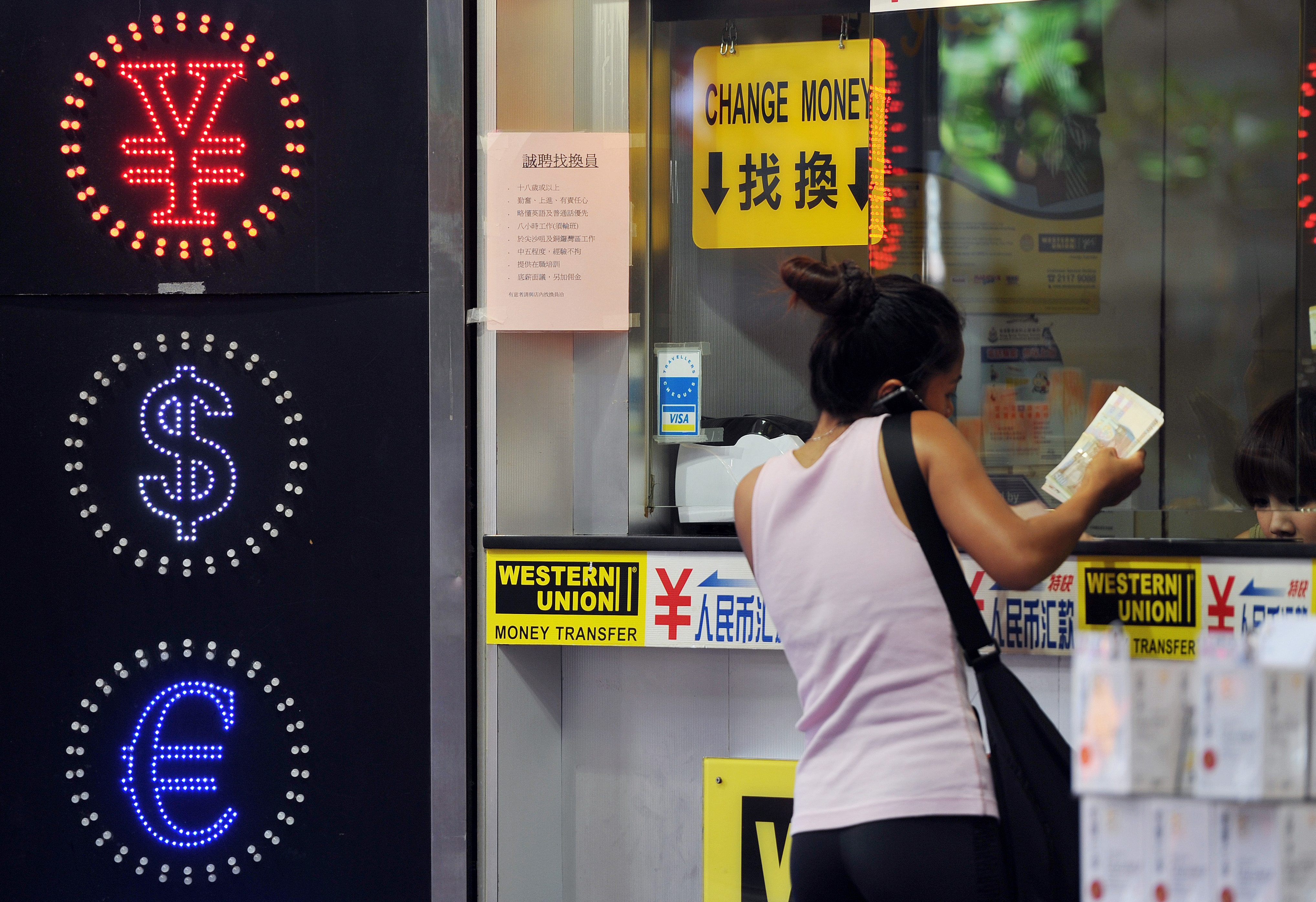 A woman exchanges money at a currency exchange shop in Hong Kong.