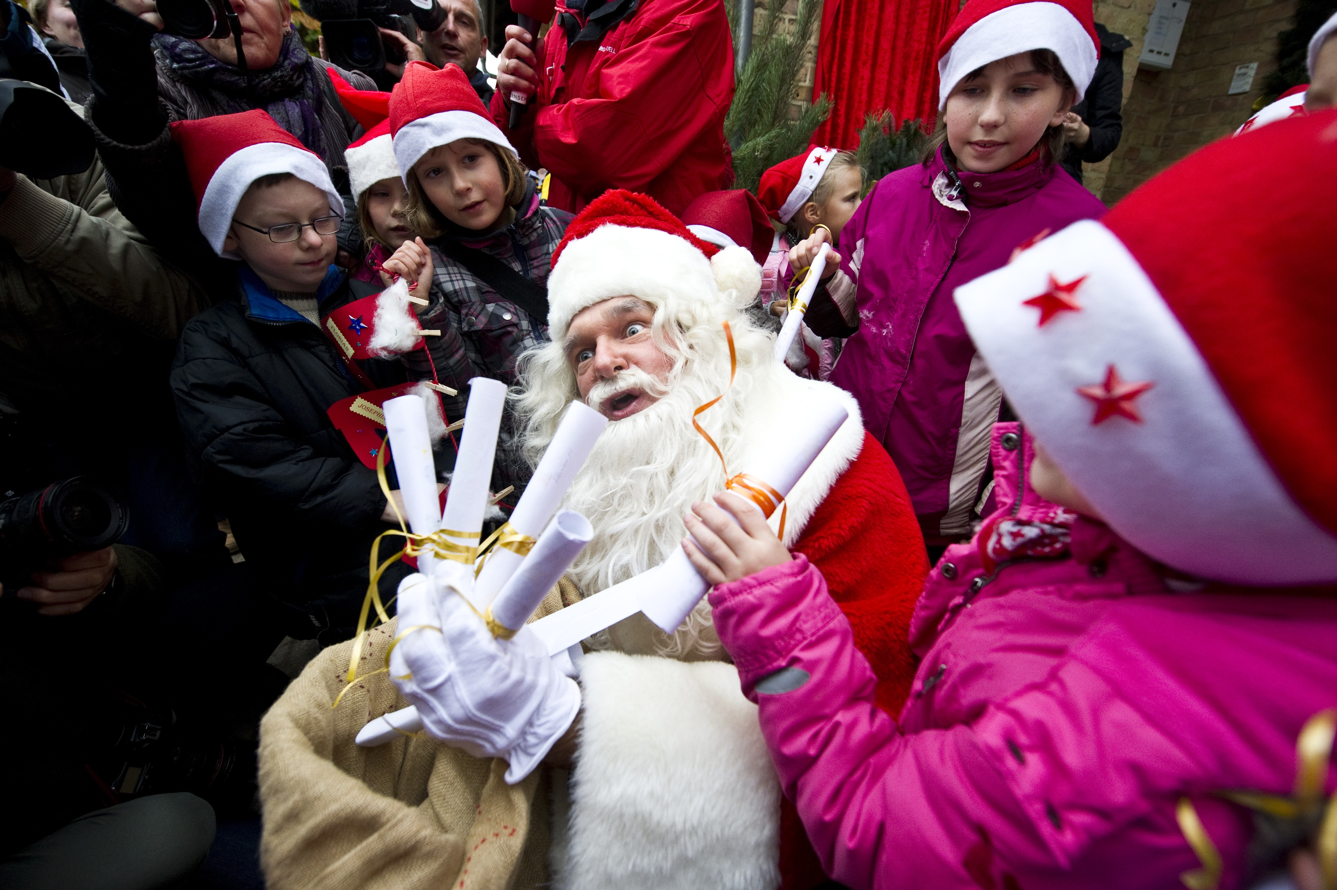A man dressed up as Santa Claus is surro