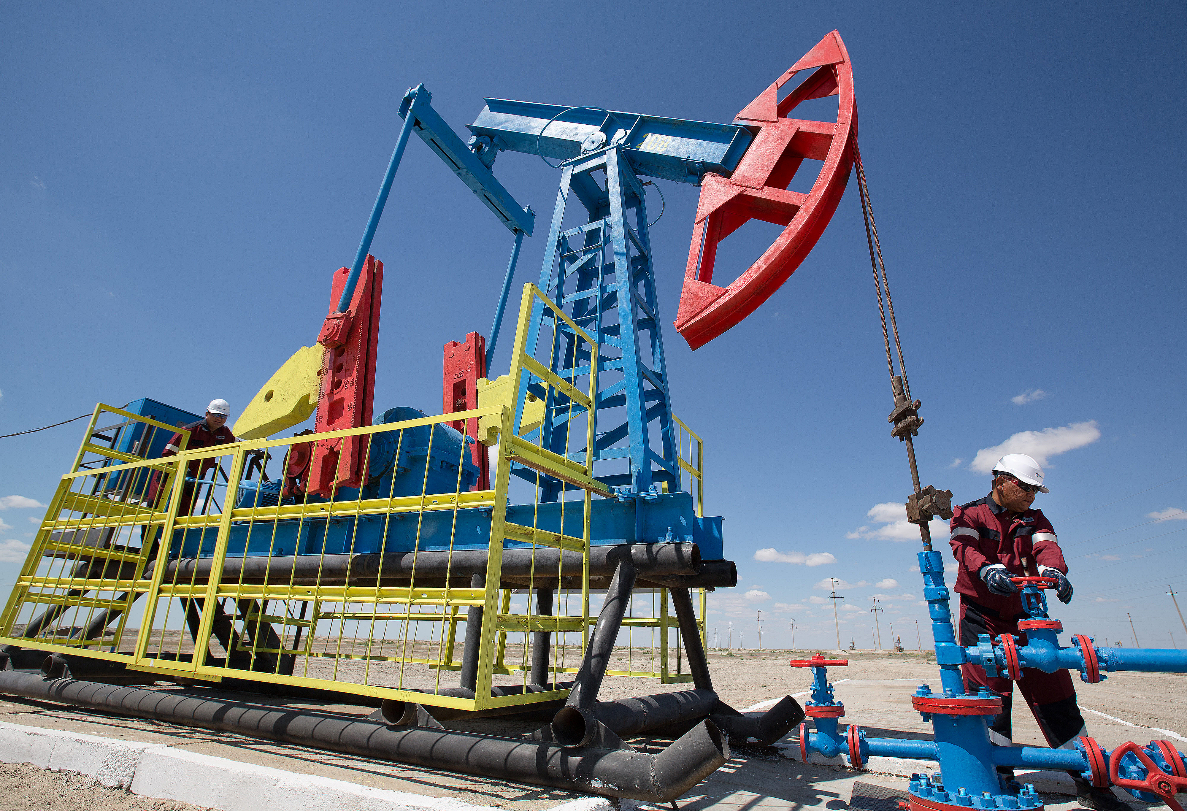 """Workers perform maintenance on an oil pumping unit, also known as a """"nodding donkey"""" at an oilfield operated by Embamunaigas, a unit of KazMunaiGas Exploration Production, in Akkystau village, near Atyrau, Kazakhstan, on Saturday, July 4, 2015. The majority Muslim country is central Asia's biggest oil producer. Photographer: Andrey Rudakov/Bloomberg"""
