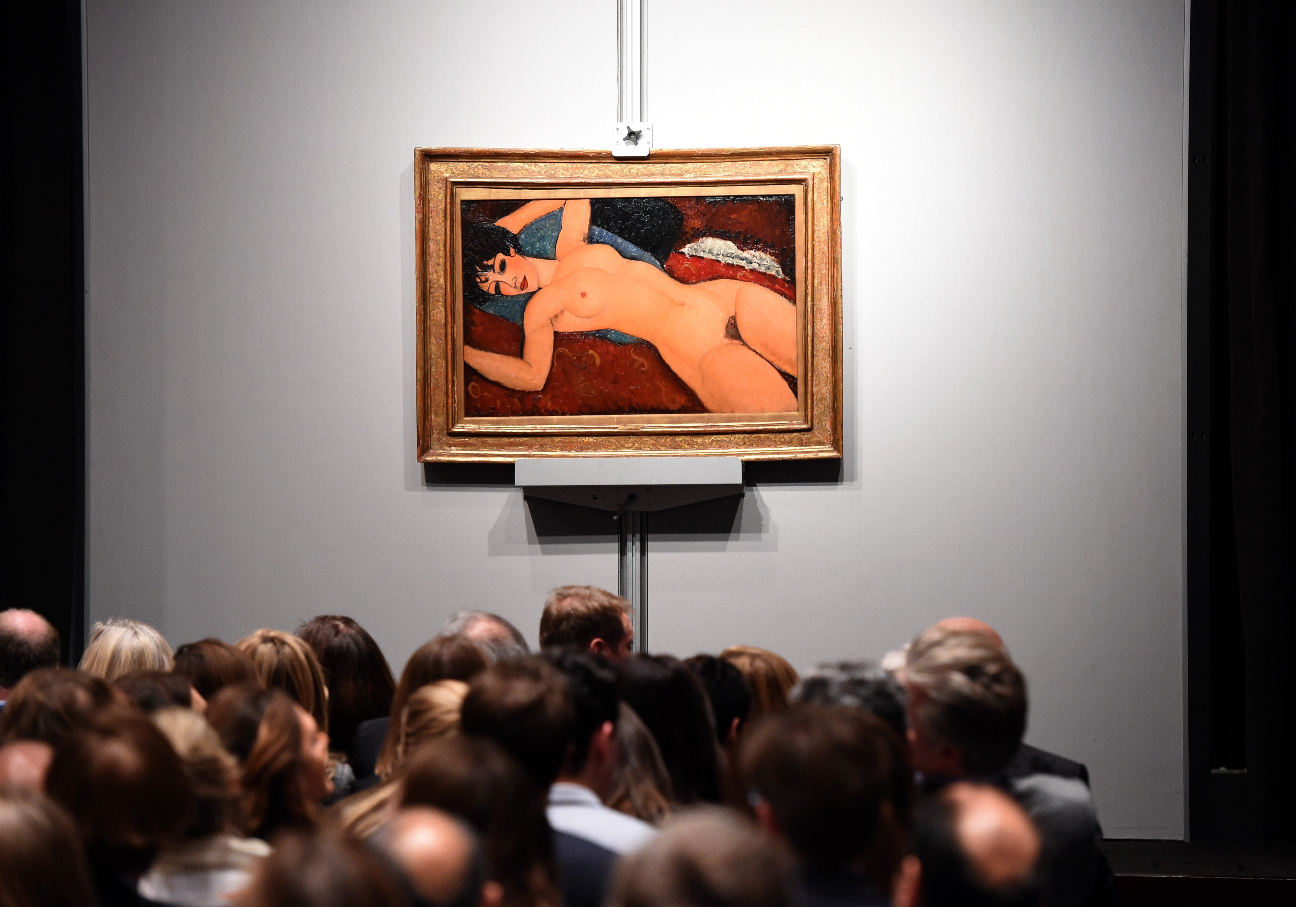 """Crowds sit in front of Amedeo Modigliani's """"Nu couche"""" at Christie's in New York on  November 9, 2015."""