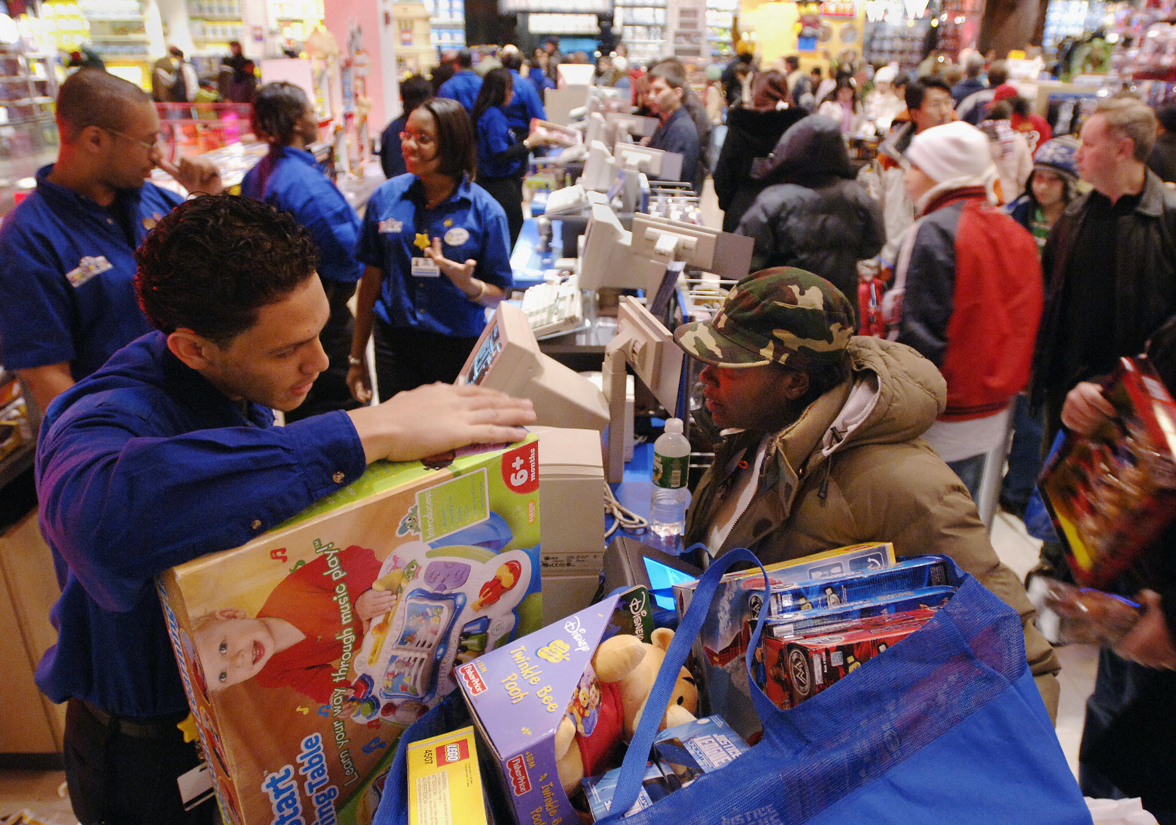 A parent buys Christmas gifts for her three children at a Toys R Us store in New York's Times Square.