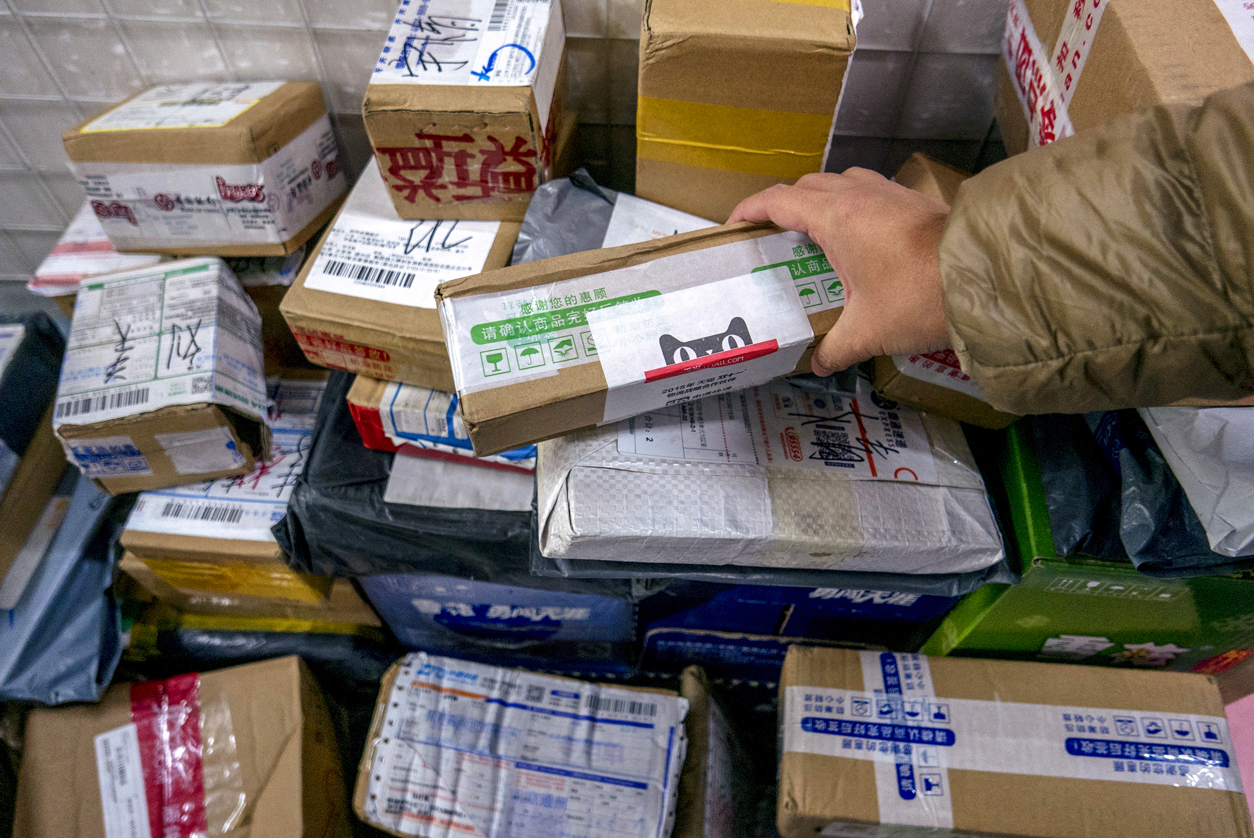 Packages are piled up in a small shop's Cainiao service