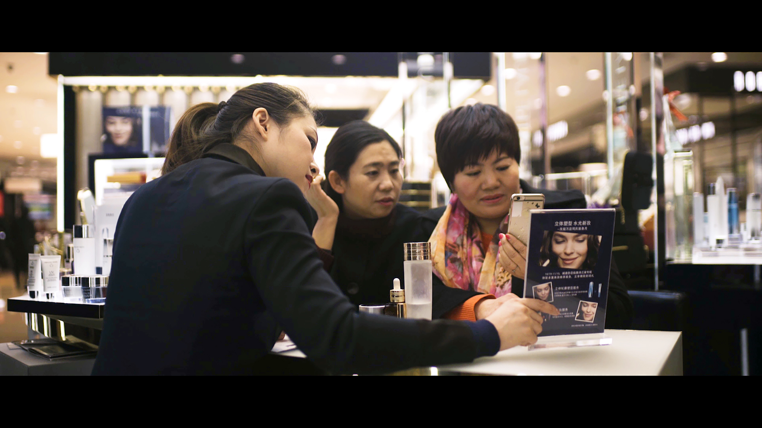 Chinese shoppers read about an Alibaba promotion at an Estée Lauder store.