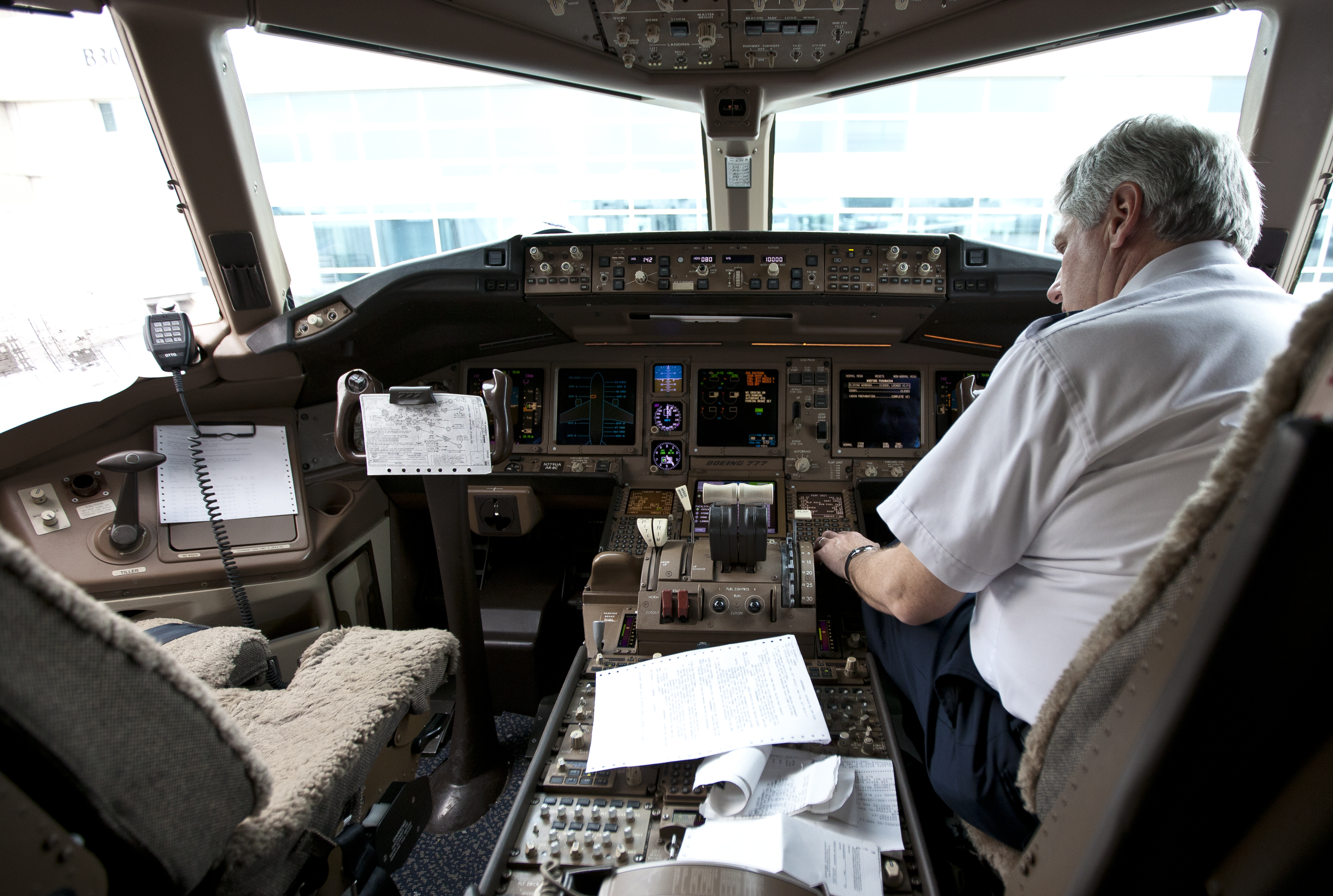 Pilot in the cockpit of a Boeing 777 at Denver International Airport.