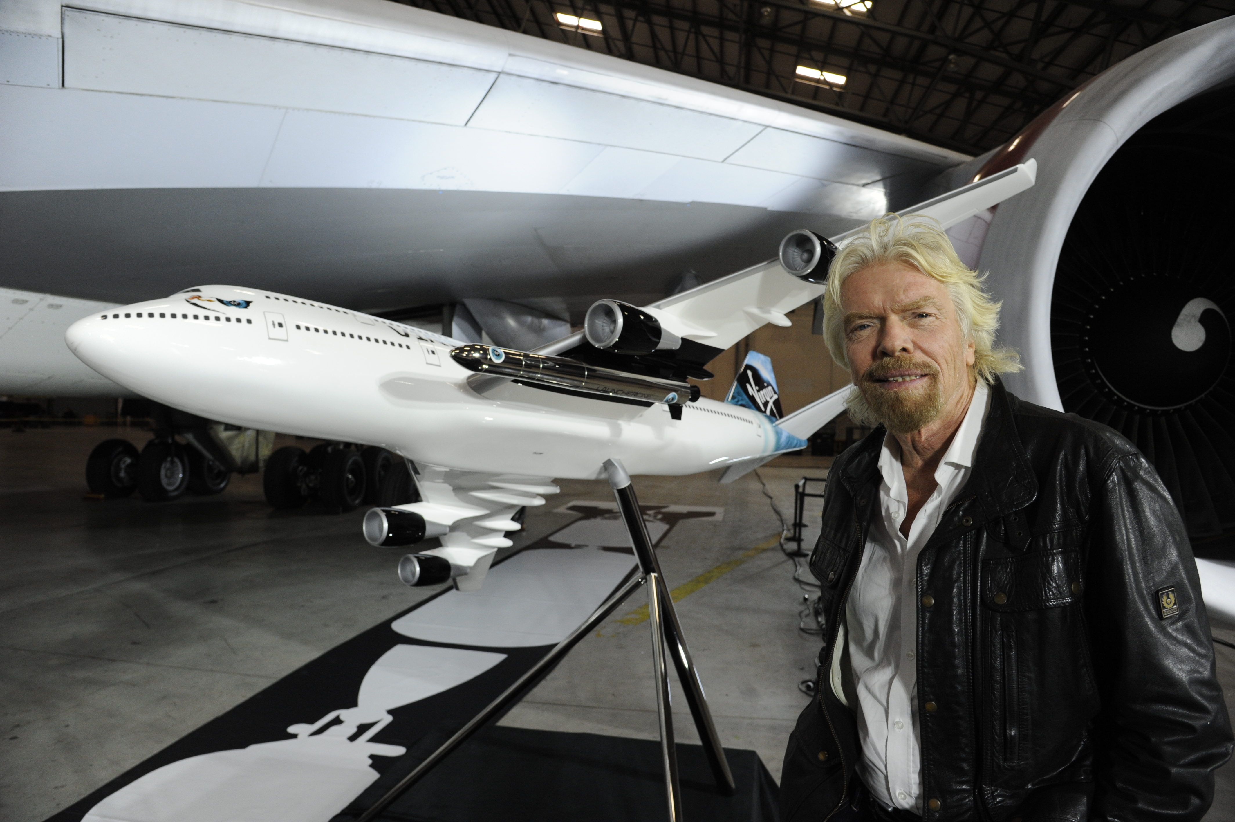 Virgin Galactic founder Richard Branson in front of a model of the repurposed Boeing 747 that will be used to launch the LauncherOne rocket.
