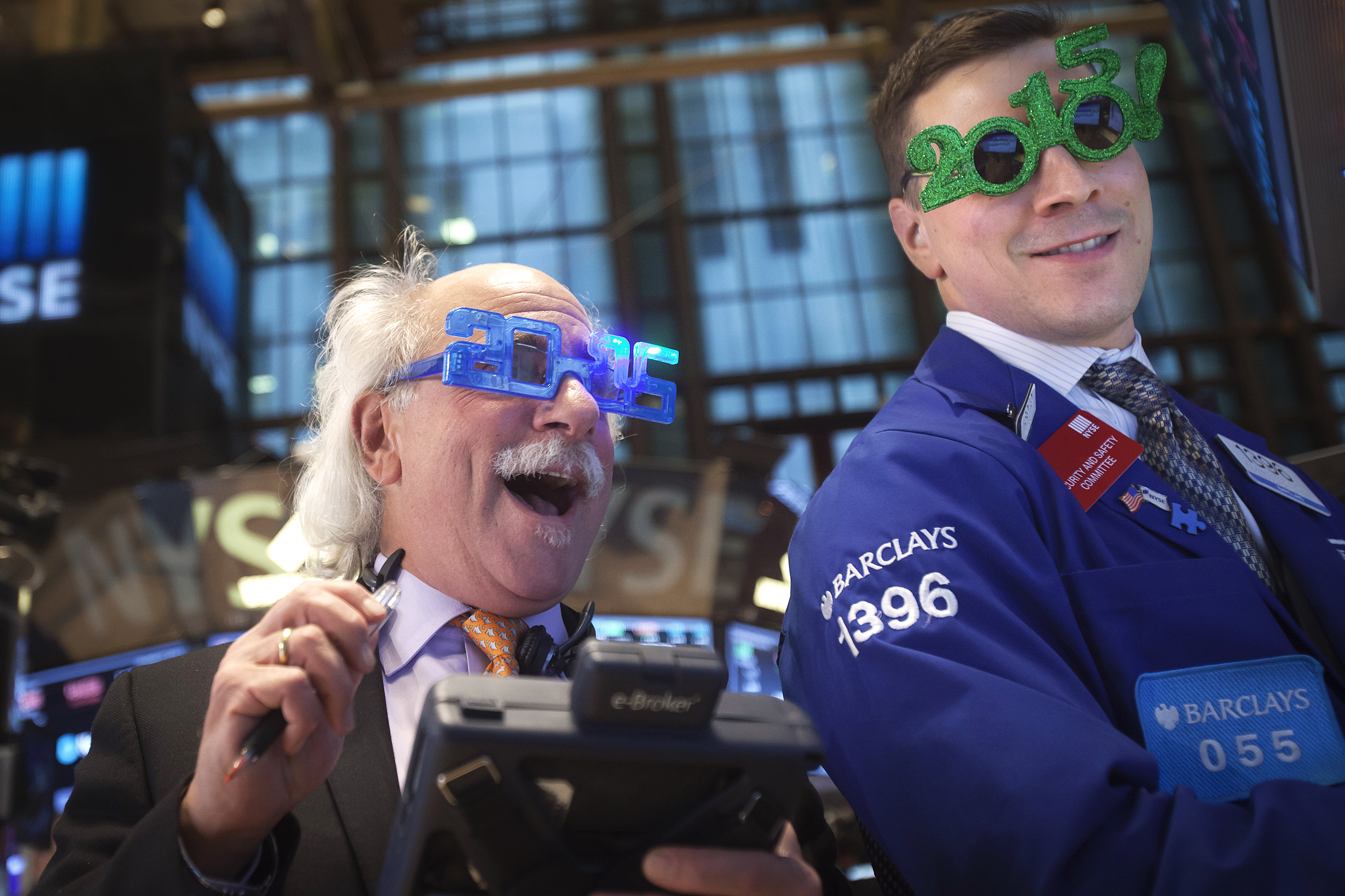 Traders Tuchman and Mastrolia work on the floor of the New York Stock Exchange while wearing 2015 novelty glasses on New Year's Eve, the last trading day of the year, in New York