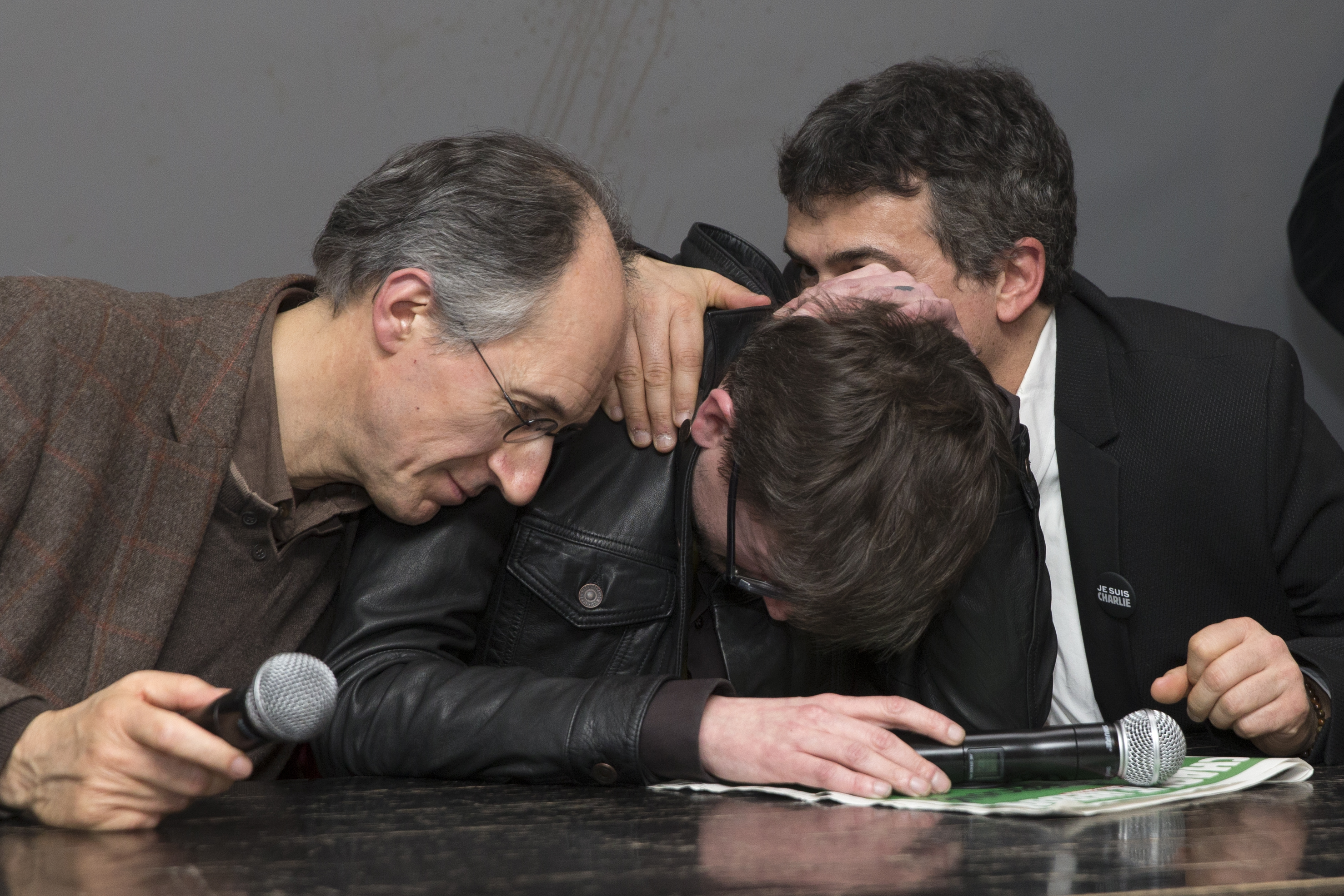 Satirical French magazine Charlie Hebdo new editor in chief Briard and columnist Pelloux comfort cartoonist Luz during a news conference at the French newspaper Liberation offices