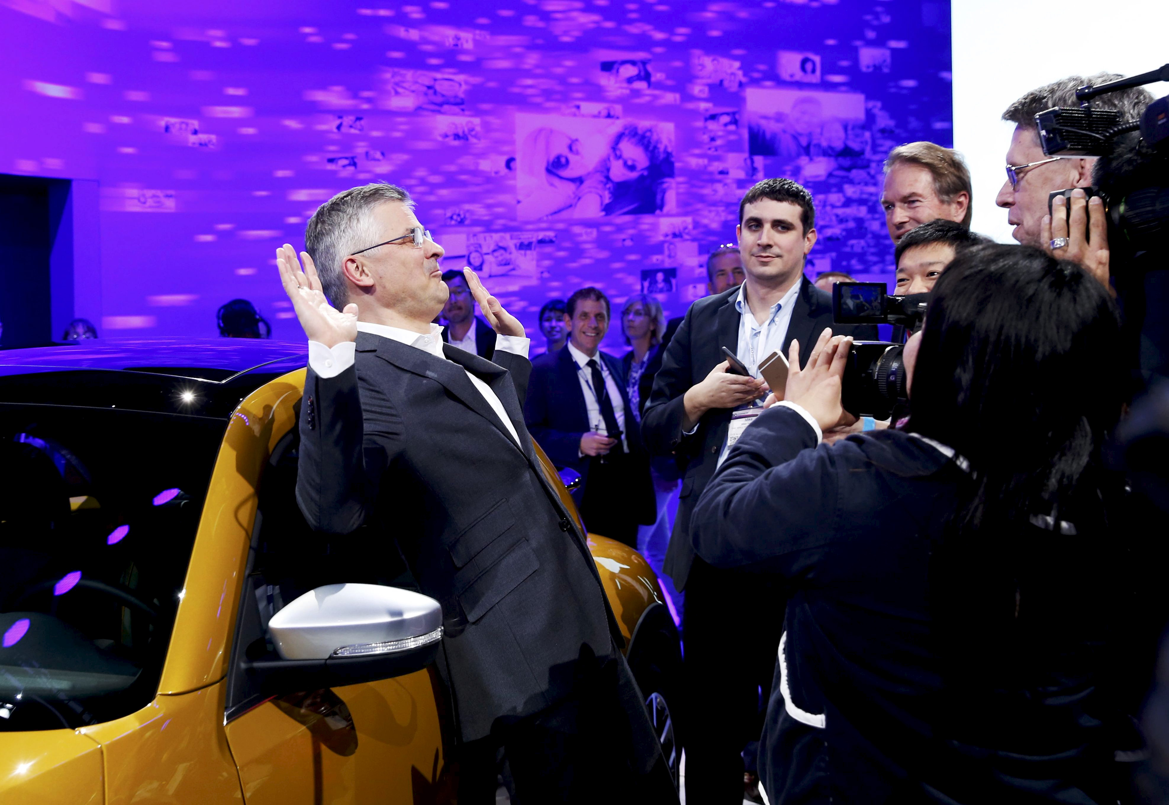 Michael Horn, President and CEO of Volkswagen America, reacts to being mobbed by the media after he apologized for the Volkswagen diesel scandal at the LA Auto Show in Los Angeles