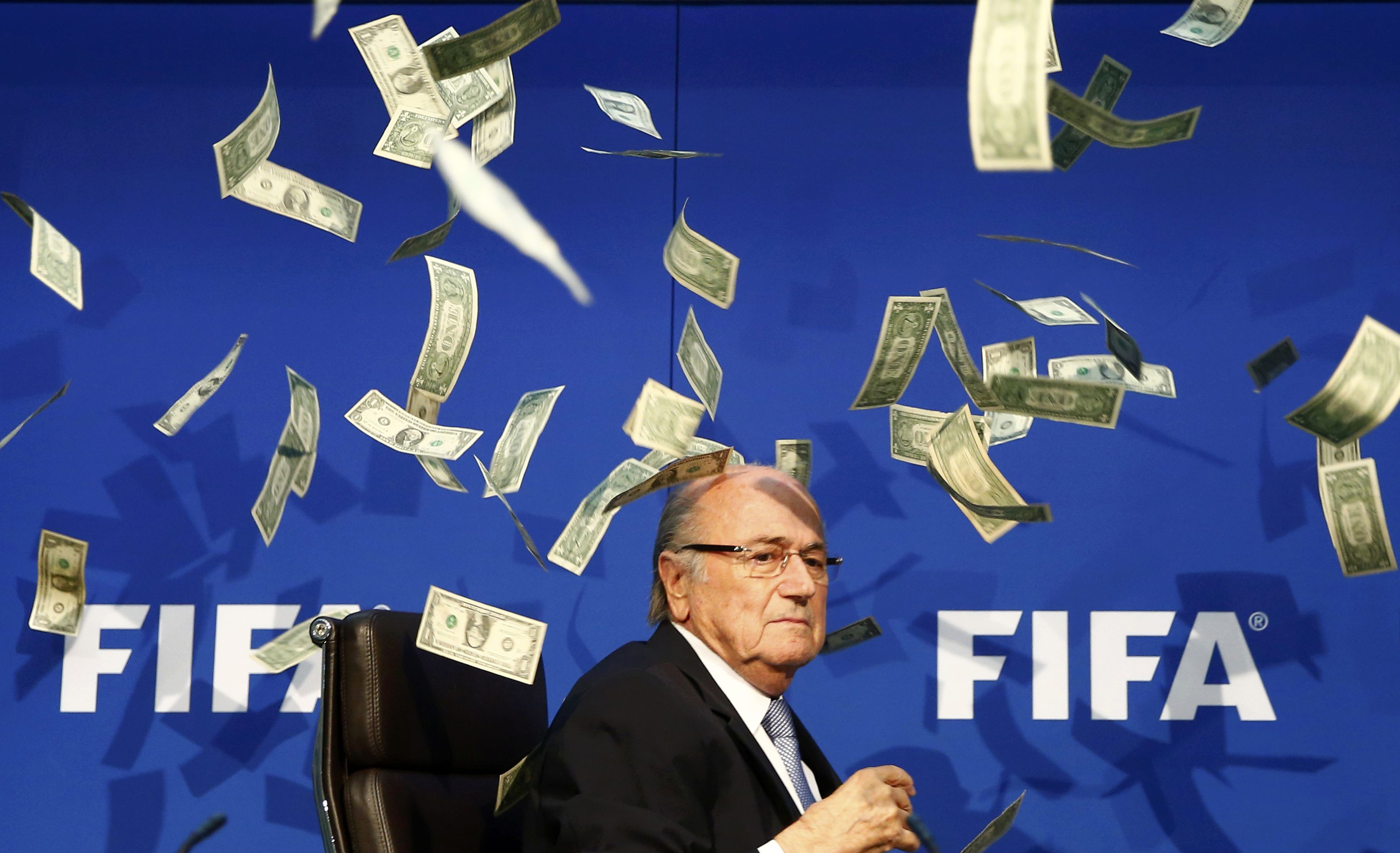 Banknotes are thrown at FIFA President Blatter as he arrives for a news conference after the Extraordinary FIFA Executive Committee Meeting at the FIFA headquarters in Zurich