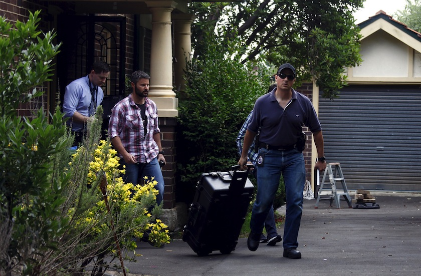 Australian Federal Police officers walk down the driveway after searching the home of probable creator of cryptocurrency bitcoin Craig Steven Wright in Sydney's north shore