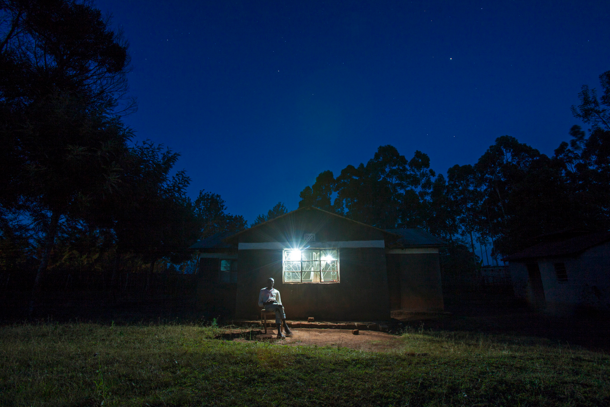 A home in Kenya, lit up by a solar panel system, sold by M-KOPA.