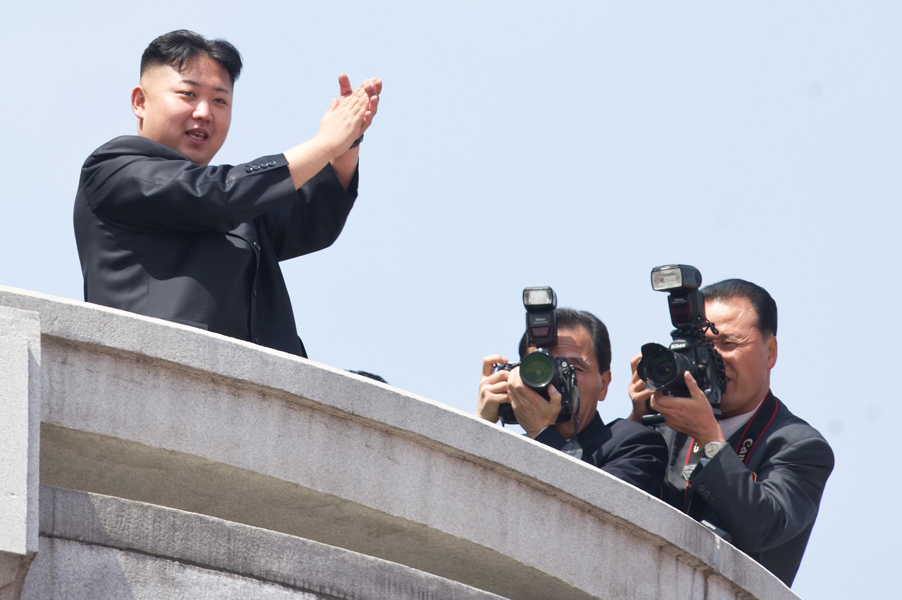 North Korean leader Kim Jong-Un (L) appl
