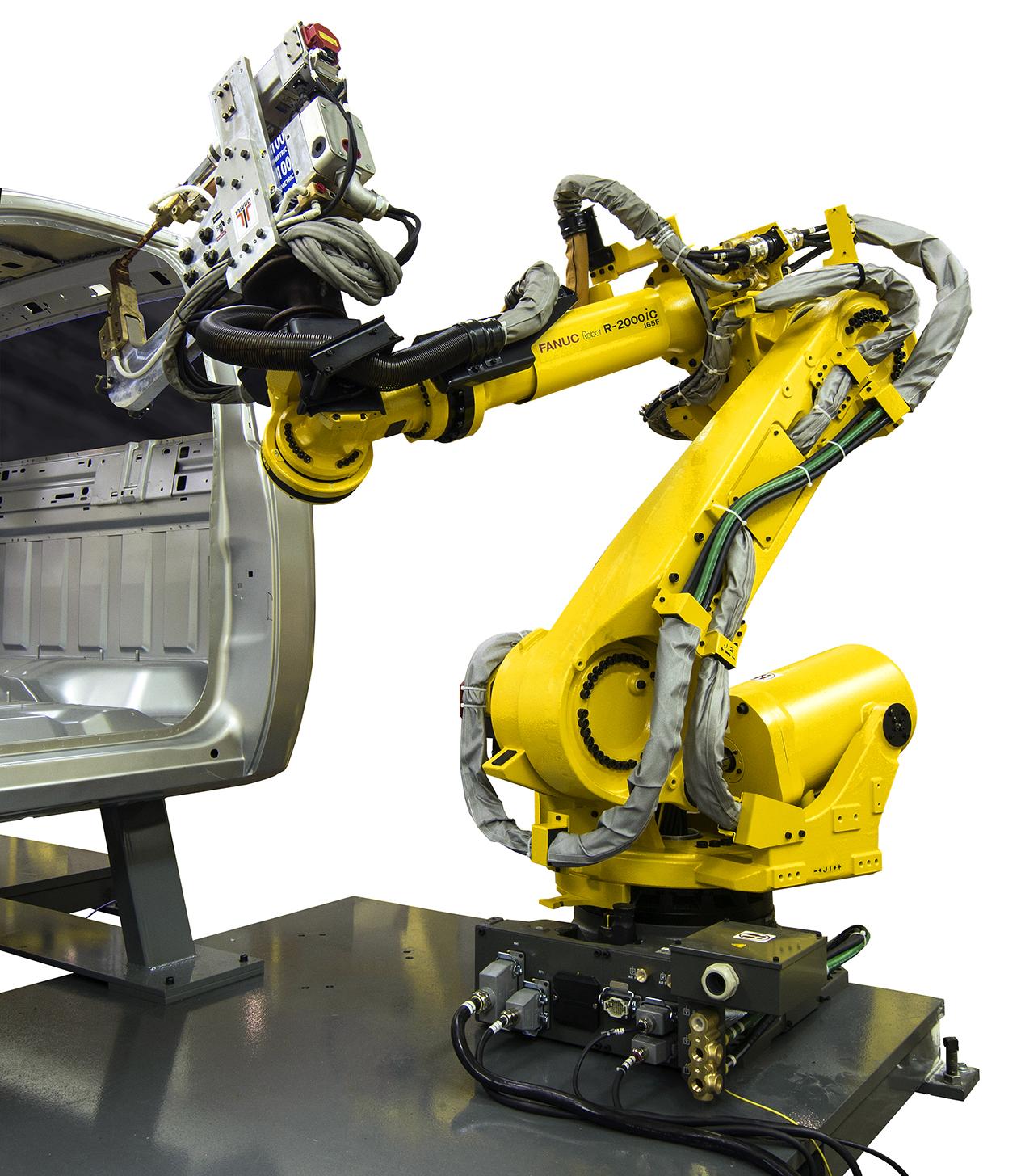 A Fanuc R-2000iC robot spot-welding the body of a truck.