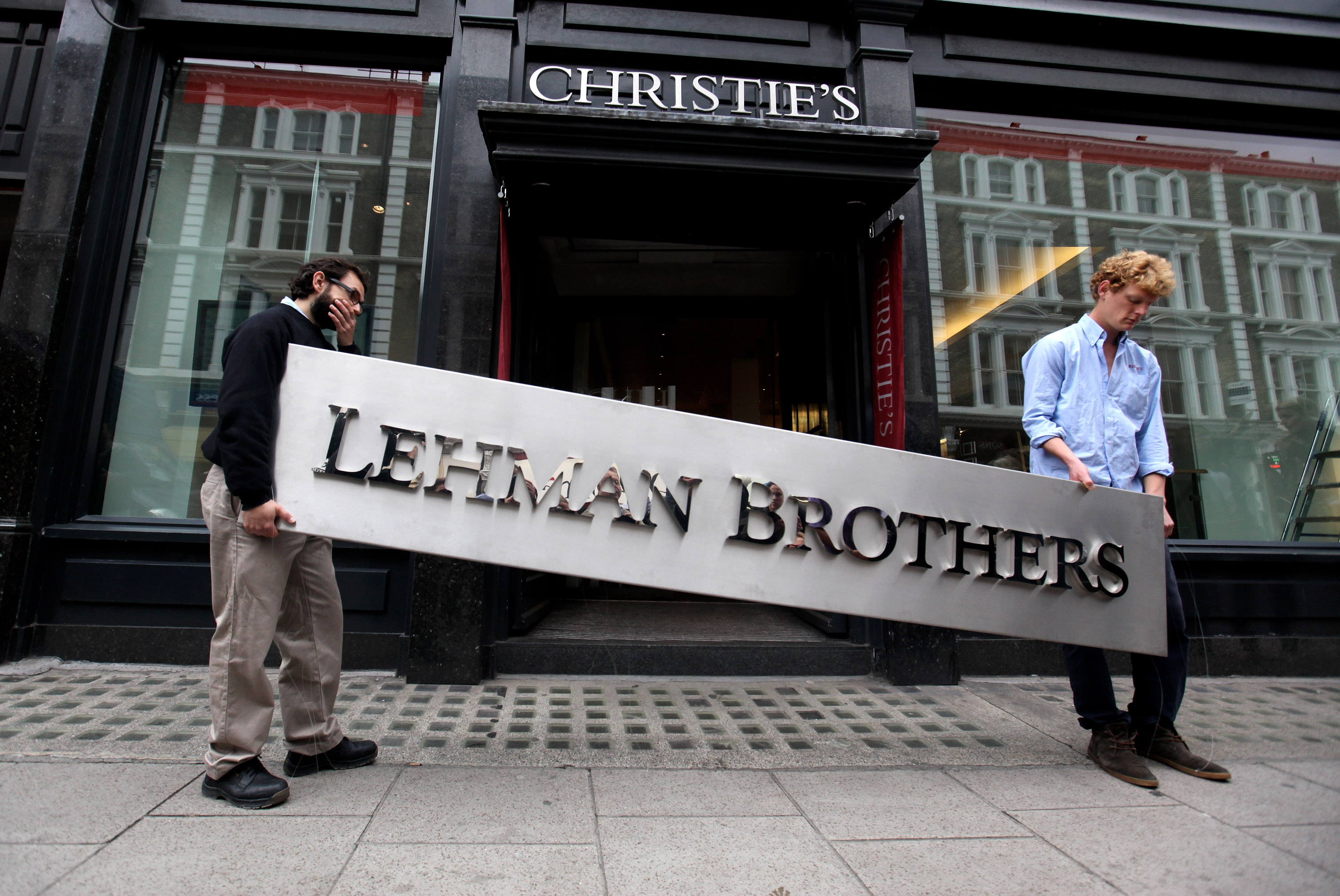 Two employees of Christie's auction house maneuver the Lehman Brothers corporate logo.
