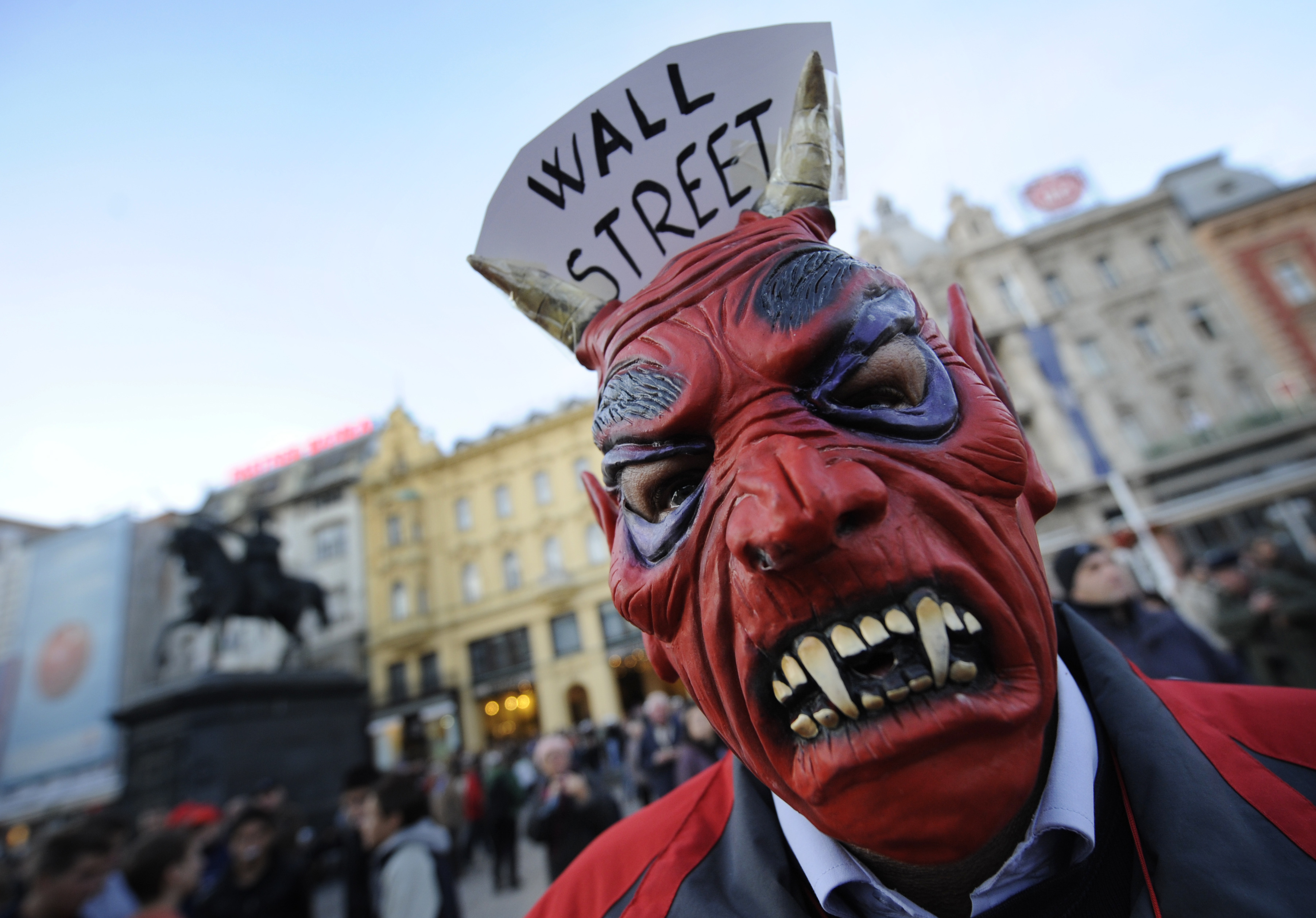"A protester wears a vampire mask with ""W"