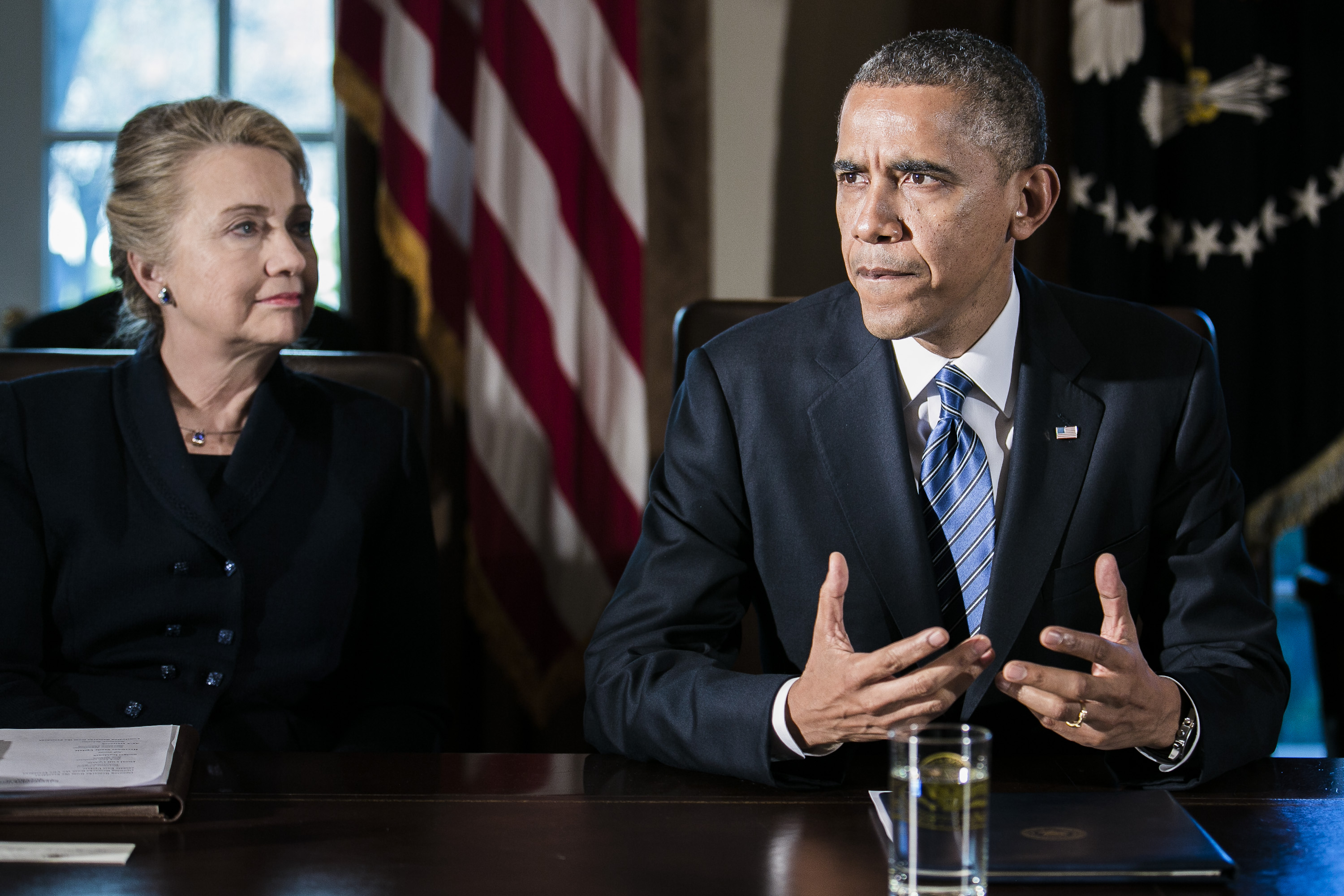 U.S. President Barack Obama, right, speaks as Department of State Secretary Hillary Clinton listens at a cabinet meeting at the White House on Nov. 28, 2012 in Washington, D.C. The president met yesterday with small business owners and today with the chief executives of major corporations in ongoing talks about the looming fiscal cliff.Photographer: T.J. Kirkpatrick/Bloomberg