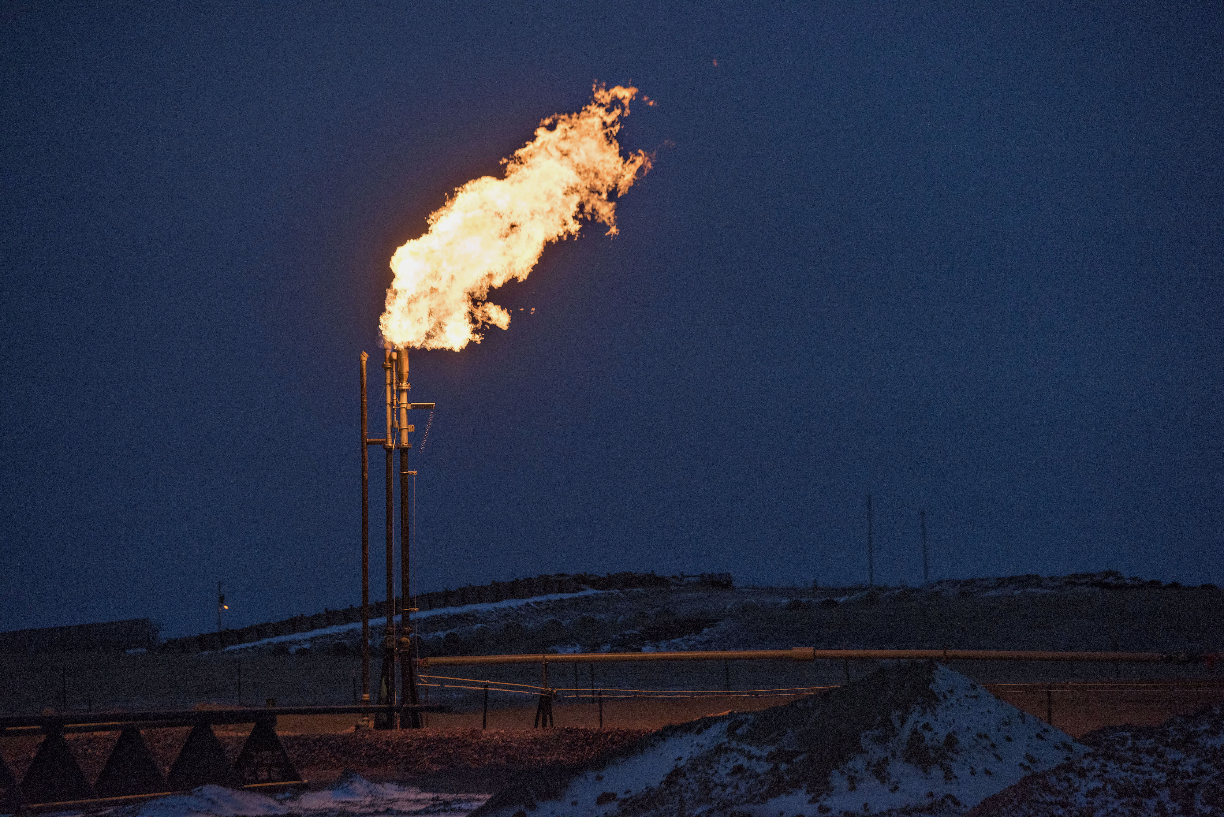A gas flare burns at an oil well site near Sidney, Montana, U.S., on Saturday, Feb. 14, 2015. Photographer: Daniel Acker/Bloomberg