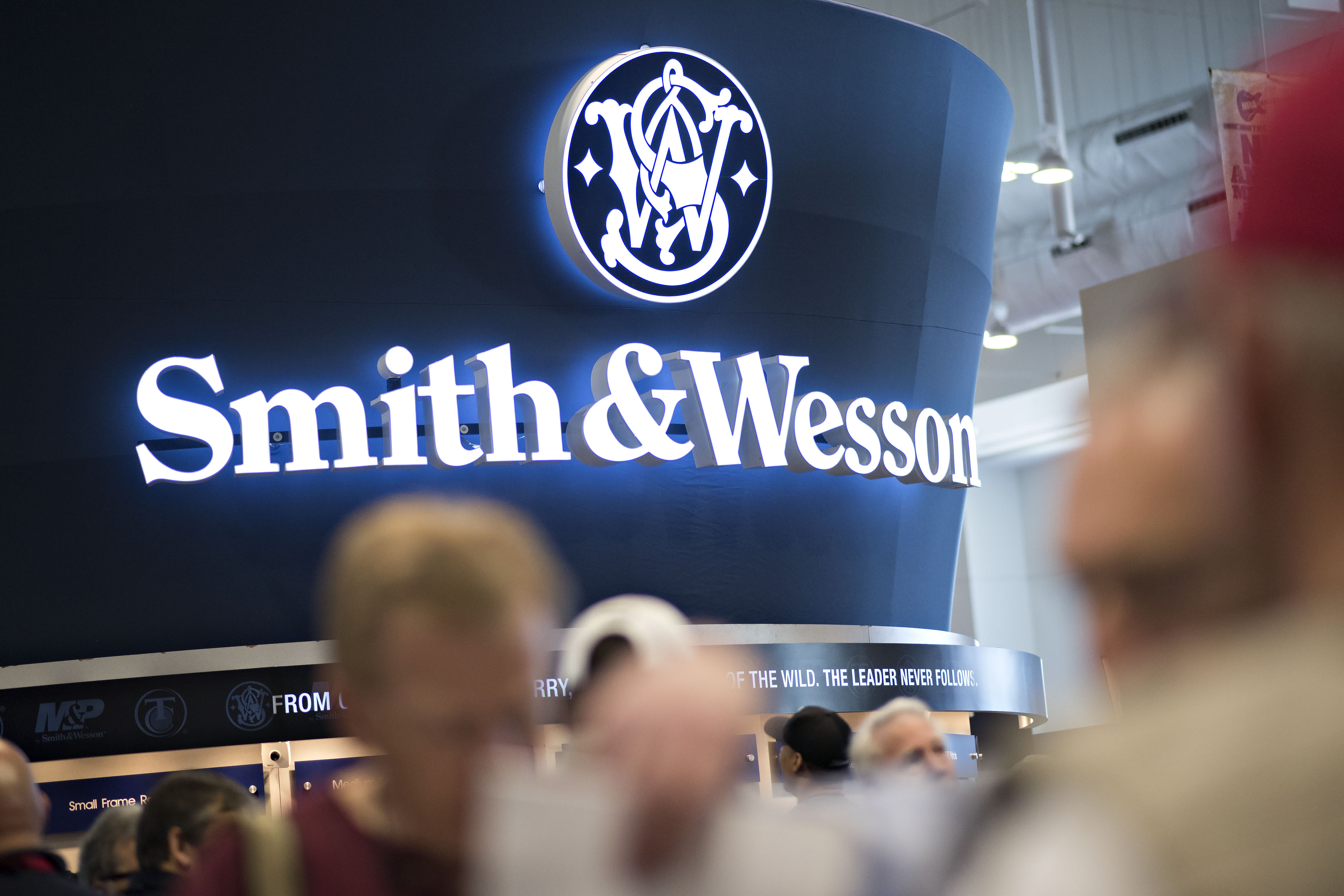Attendees look over hand guns in the Smith & Wesson booth on the exhibition floor of the 144th National Rifle Association (NRA) Annual Meetings and Exhibits at the Music City Center in Nashville, Tennessee, U.S., on Saturday, April 11, 2015. Top Republican contenders for their party's 2016 presidential nomination are lining up to speak at the annual NRA event, except New Jersey Governor Chris Christie and Kentucky Senator Rand Paul, who were snubbed by the country's largest and most powerful gun lobby. Photographer: Daniel Acker/Bloomberg via Getty Images