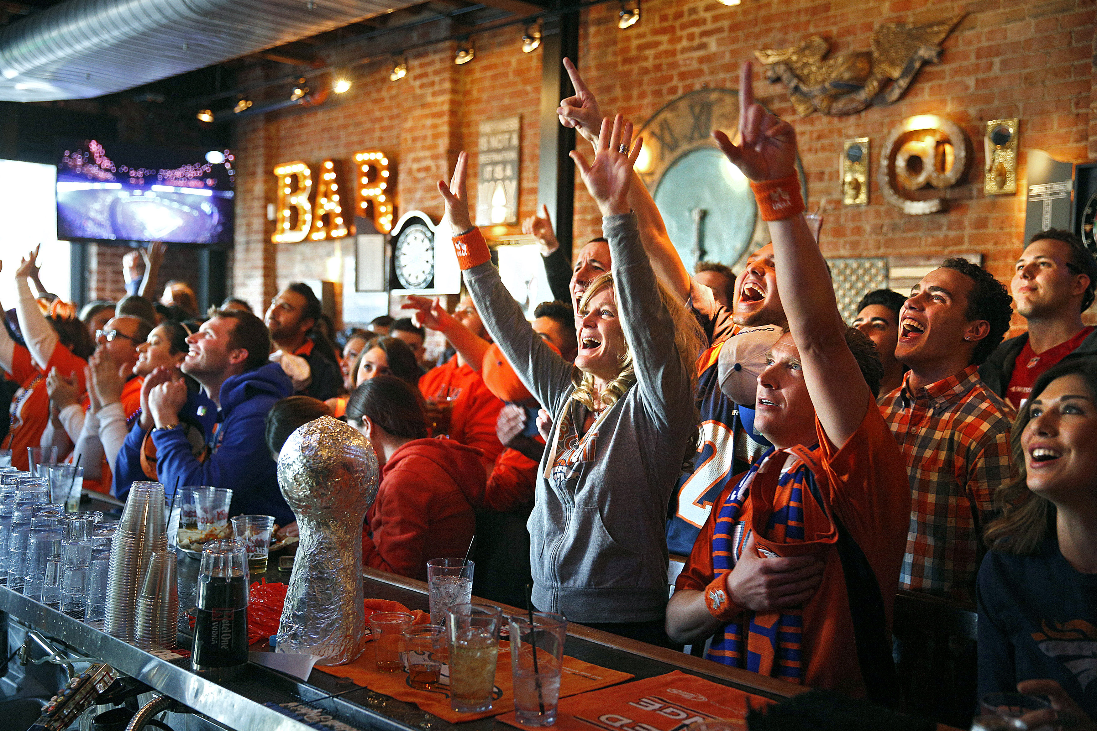 Broncos fans cheer as their team takes the field against the Seahawks while watching the NFL Super Bowl XLVIII football game at a bar in Denver