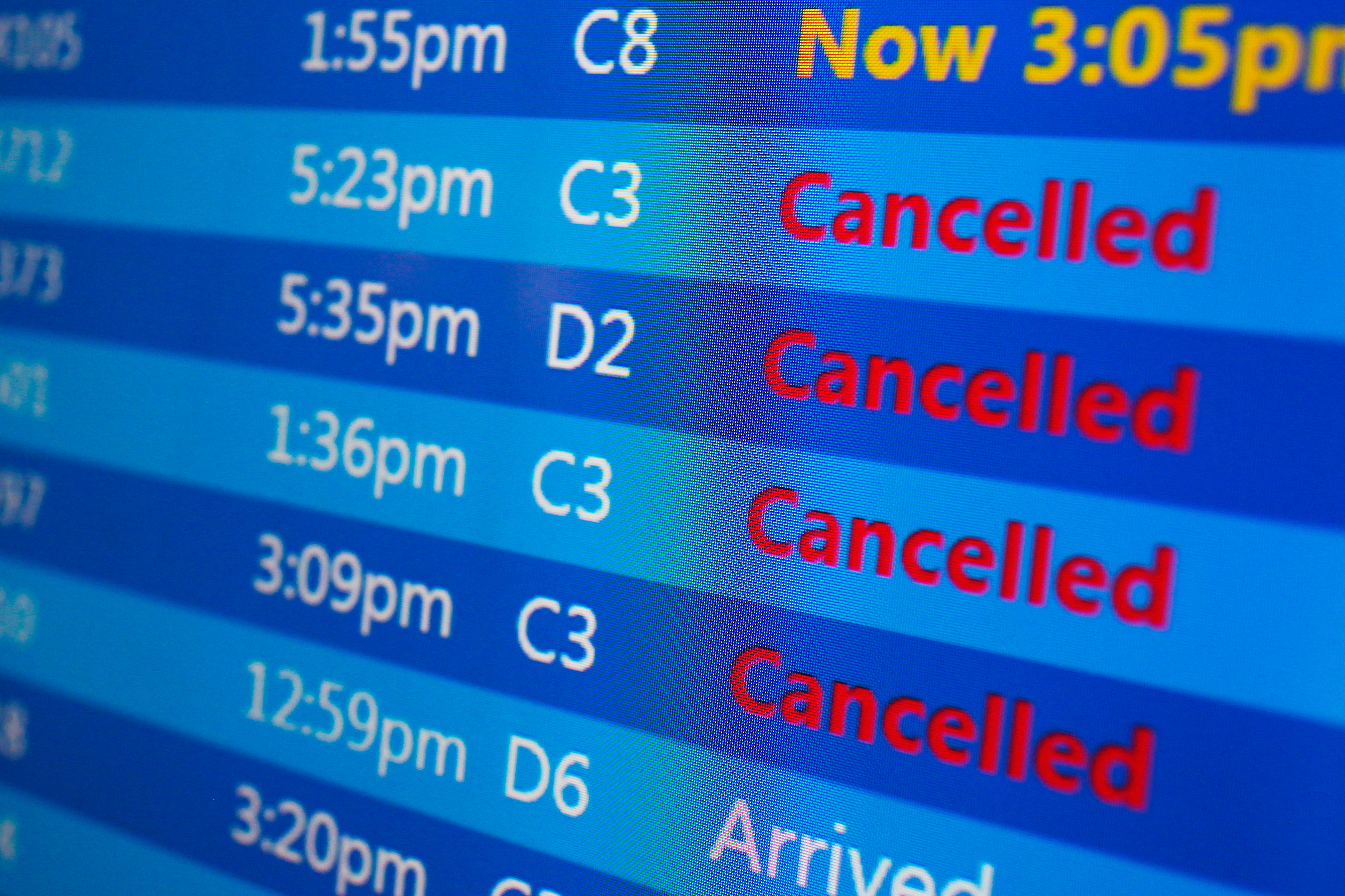 Cancelled flights are displayed on a status board at New York's Laguardia Airport ahead of a powerful approaching winter storm