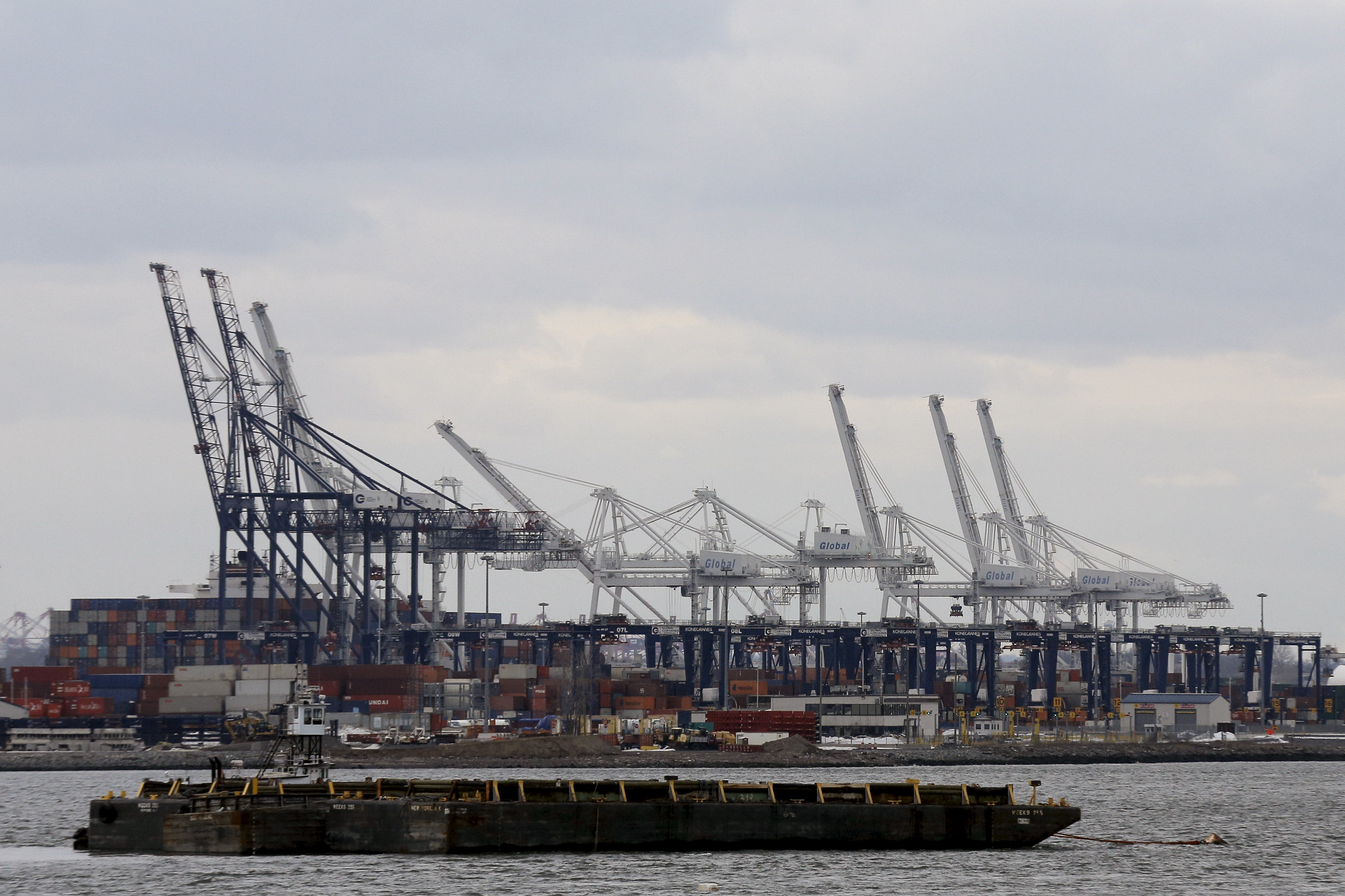 A barge is seen as containers are stacked at the Port in Bayonne, New Jersey during a work stoppage in the harbor of New York