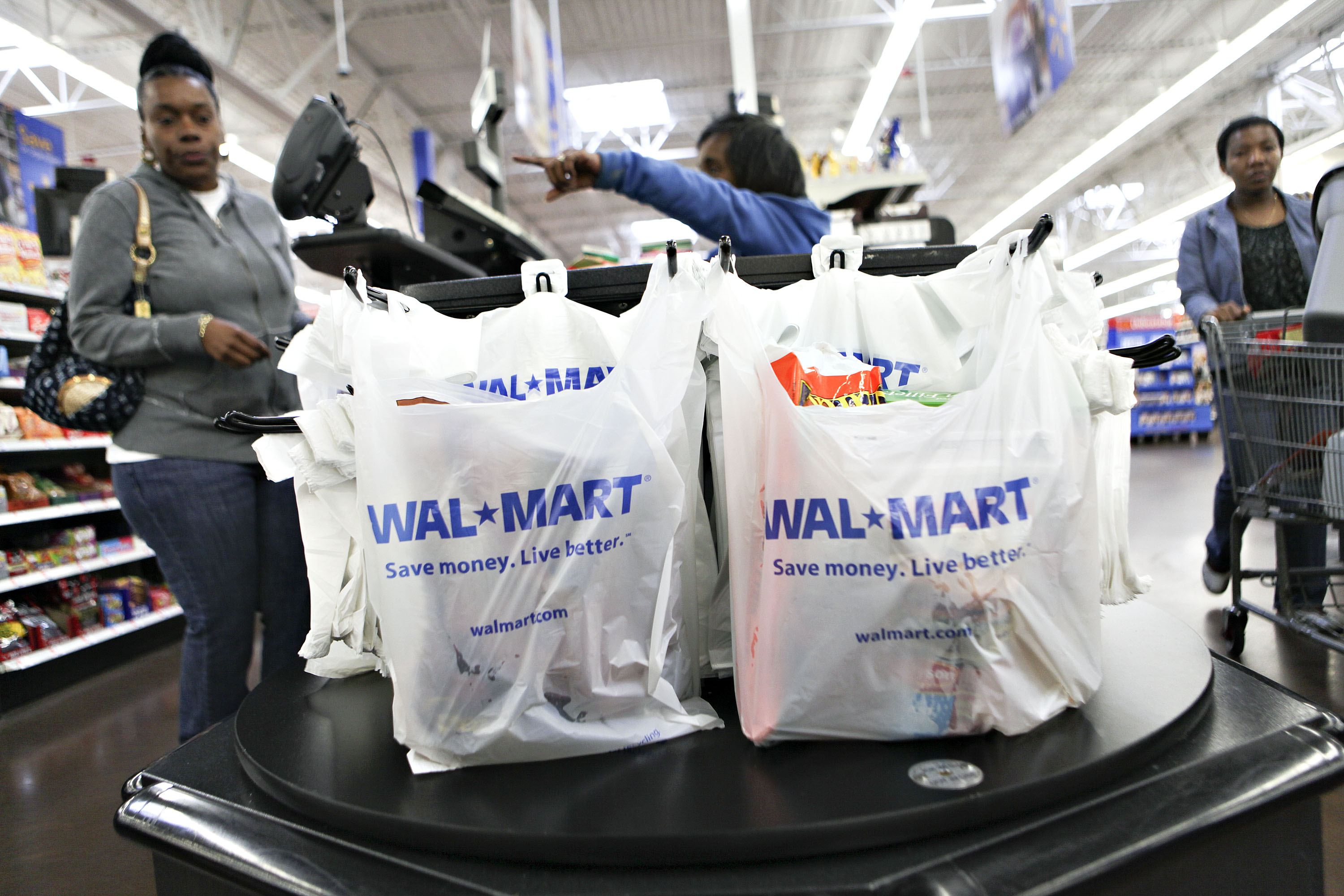 Wal-Mart logos apprear on shopping bags at a cash register i