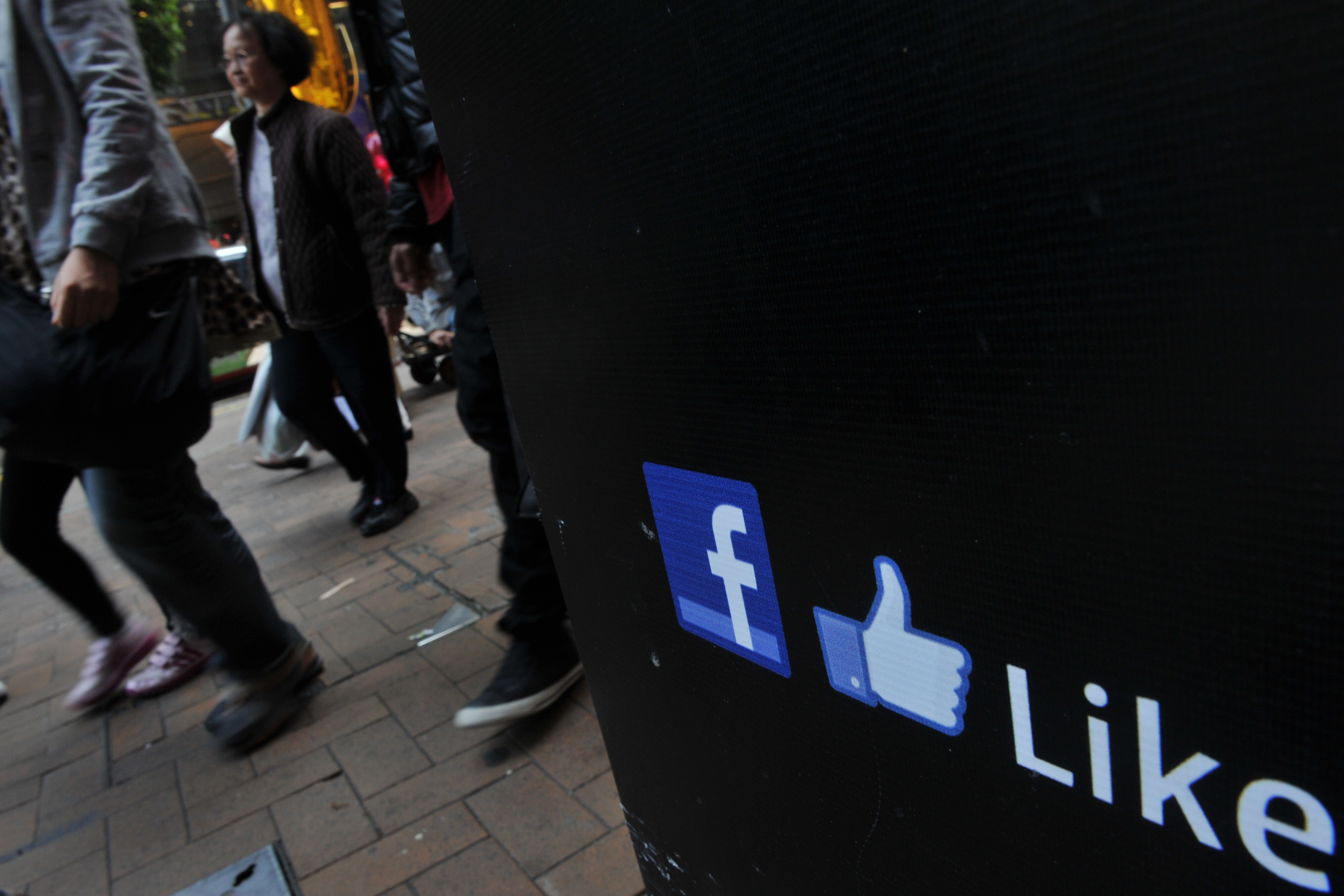 People walk by a Facebook logo and a thu