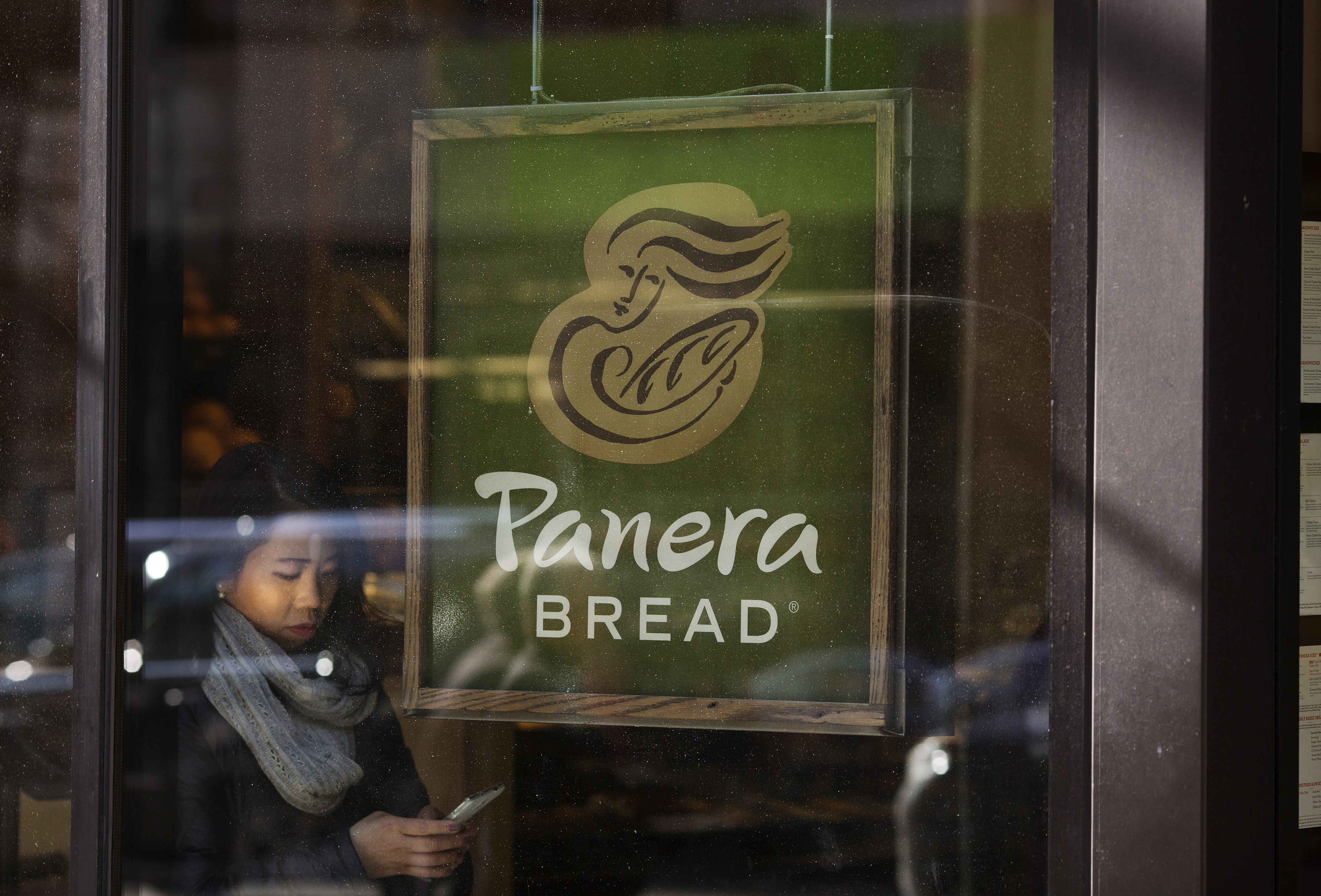 Pedestrians walk by a Panera Bread restaurant in Midtown Manhattan, New York, NY, Tuesday, February 10, 2015.