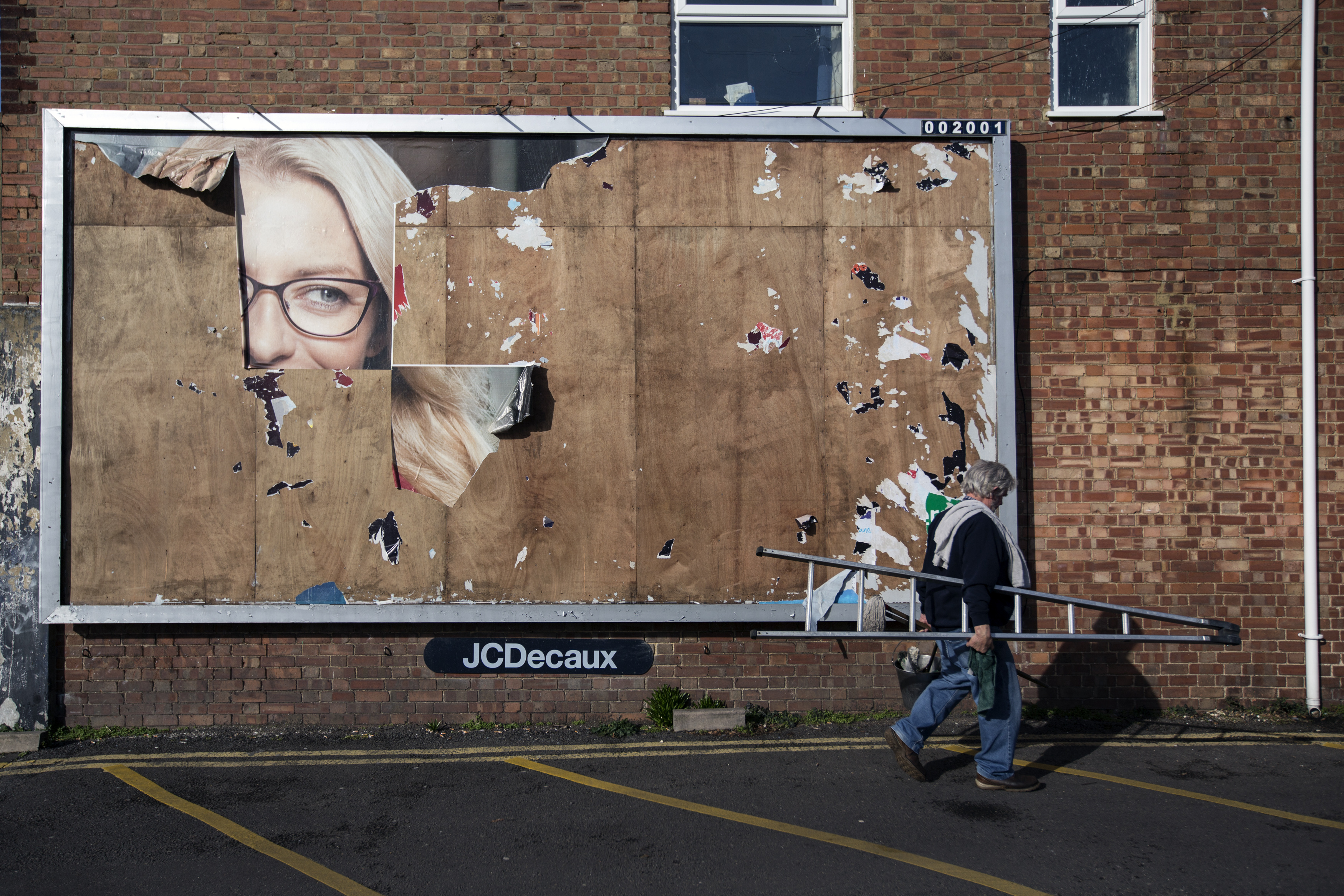 A Man Walks Past the Remains of an Old Billboard Advert