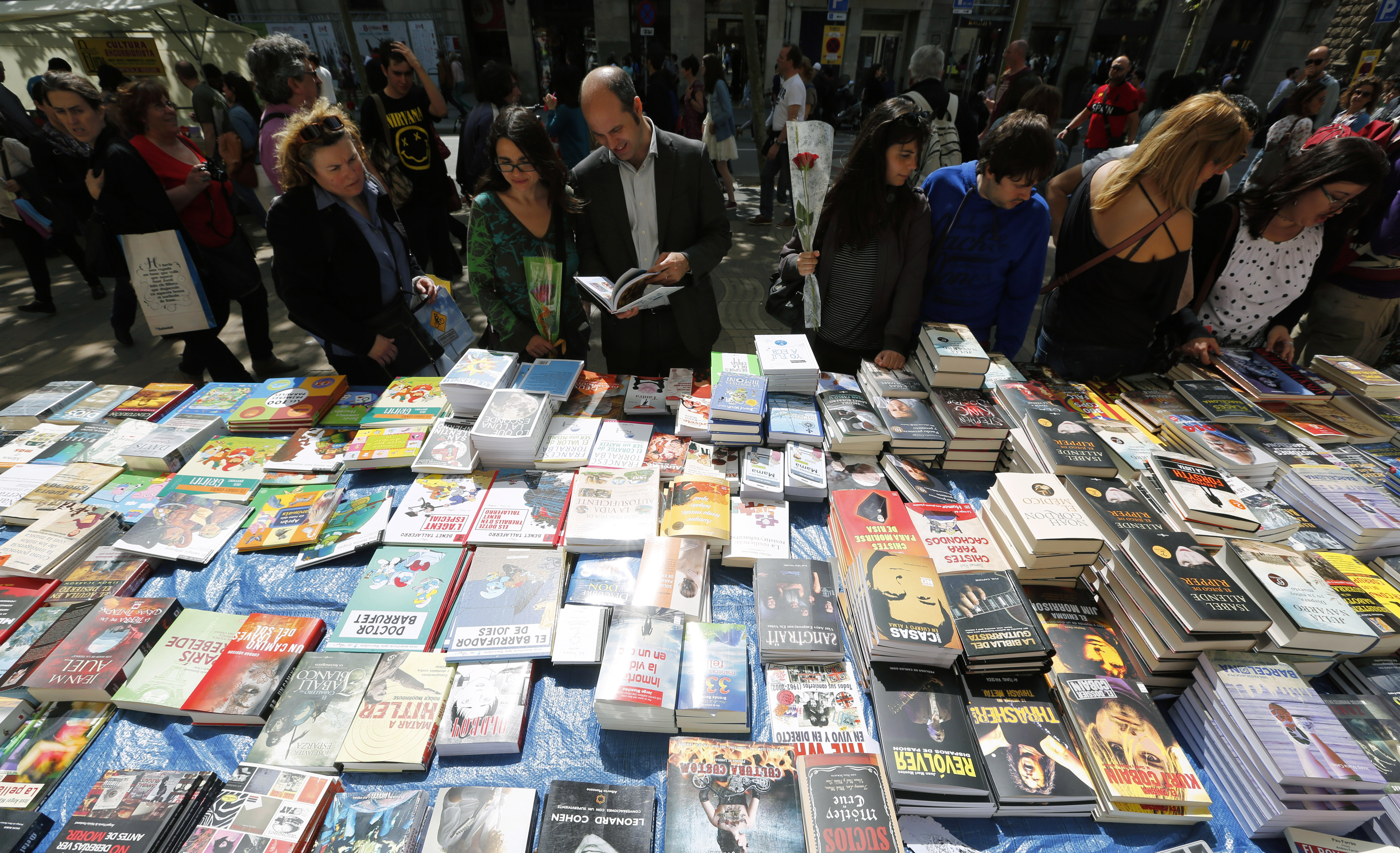 People look books in a stand at Las Ramblas street during traditional Sant Jordi's day celebrations in Barcelona