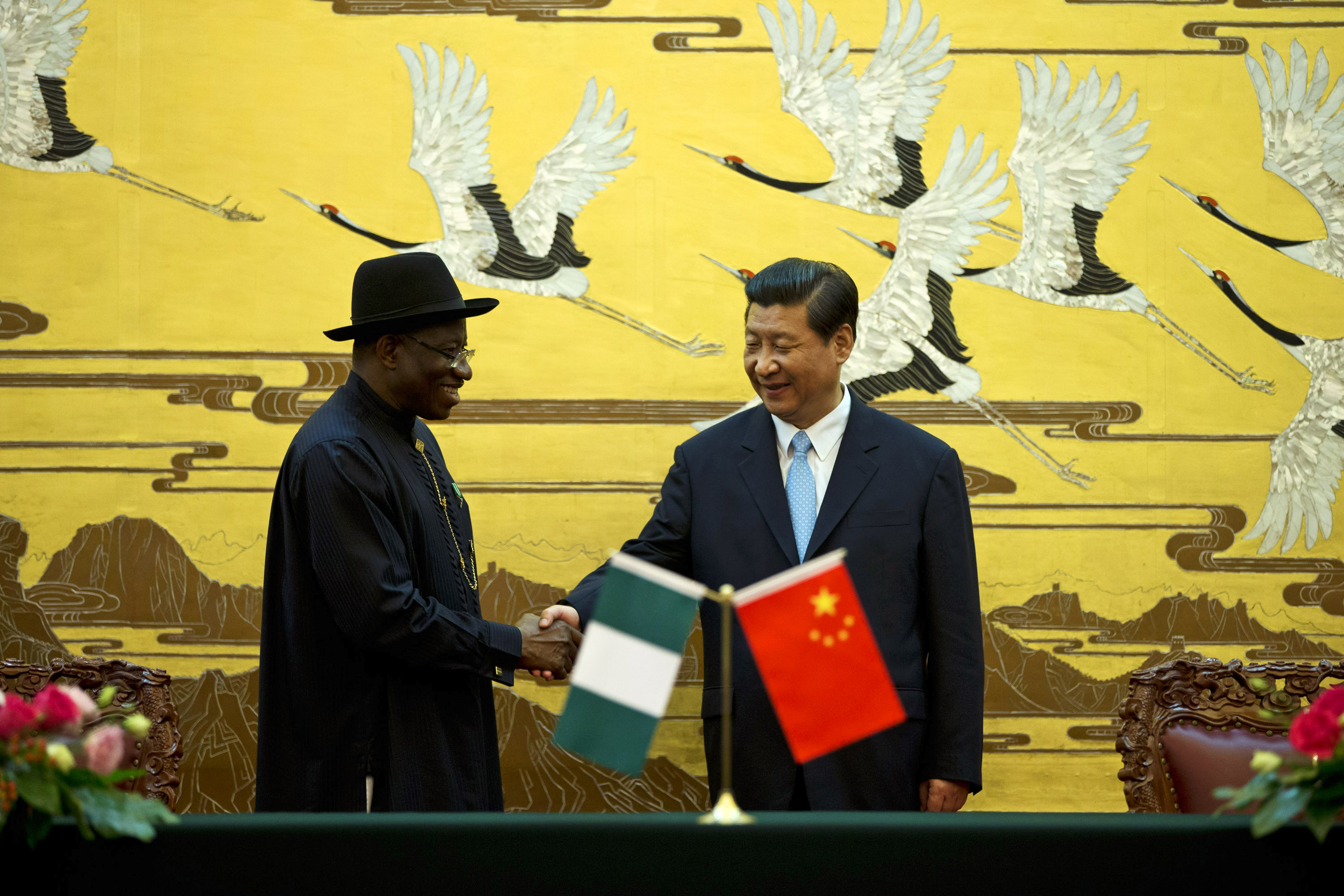 Chinese President Xi shakes hands with Nigerian President Jonathan after their ministers signed agreements in Beijing