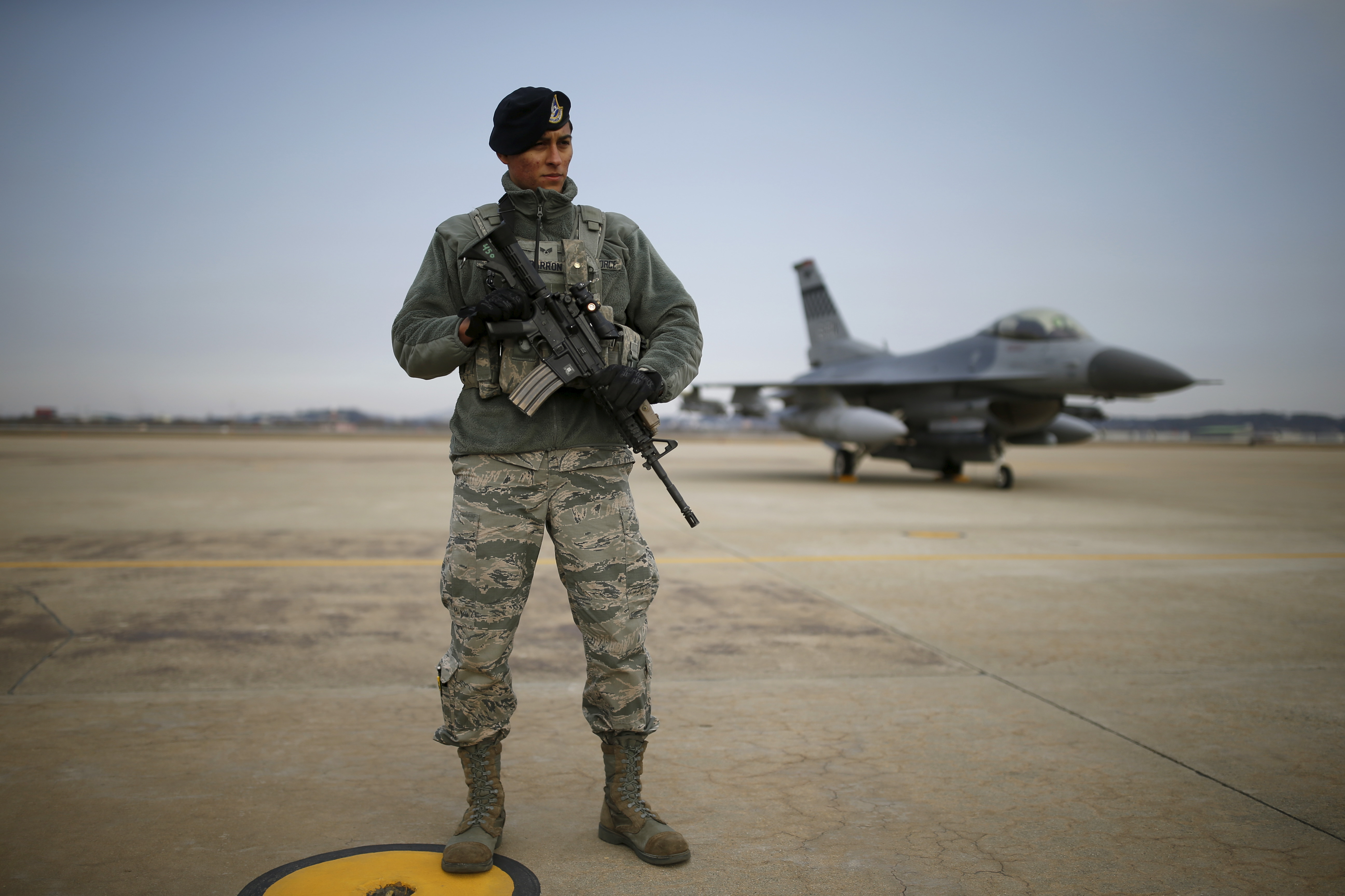 A U.S. soldier stands guard in front of their Air F-16 fighter jet at Osan Air Base in Pyeongtaek
