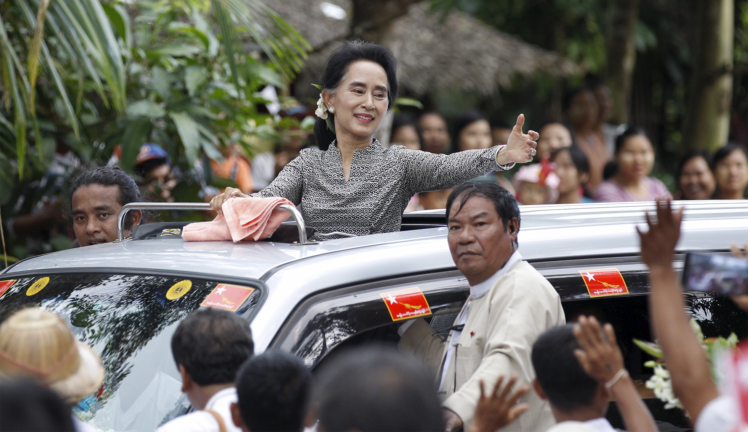 Myanmar pro-democracy leader Aung San Suu Kyi waves to supporters before giving a speech during her campaign in her constituency of Kawhmu township outside Yangon