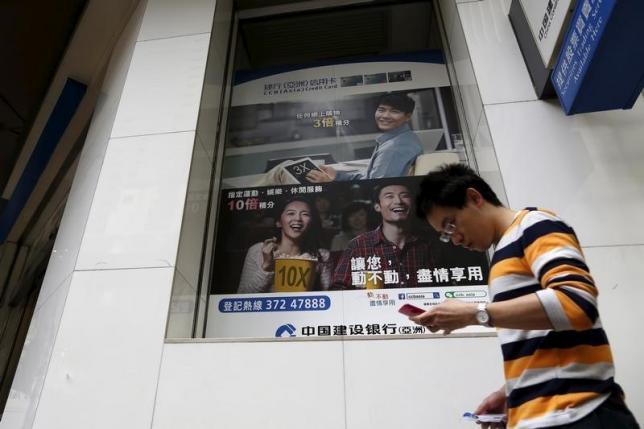 A man walks past an advertisement for young customers of China Construction Bank, in Hong Kong, China