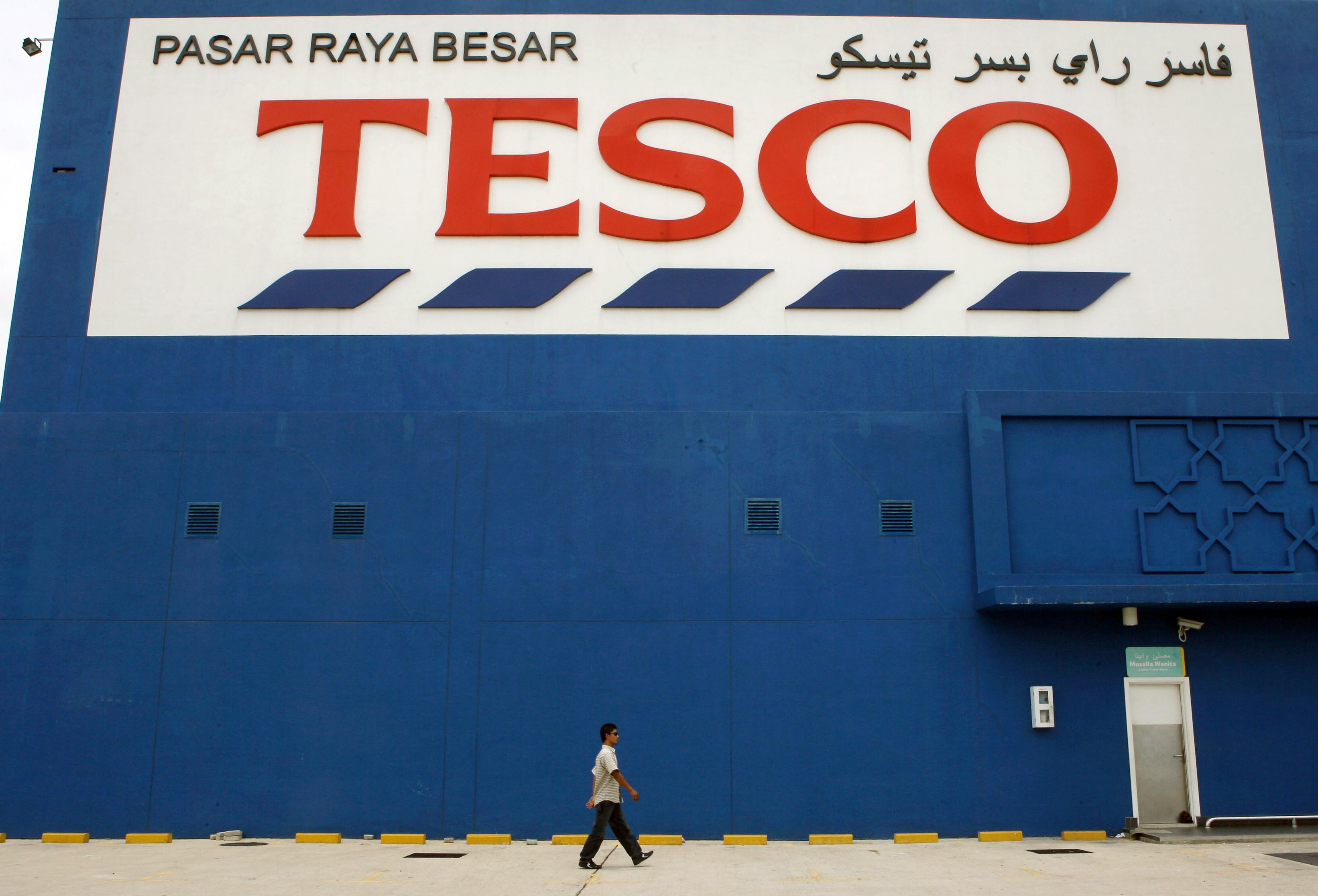 A pedestrian walks past a Tesco Plc hypermarket in Kota Bhar