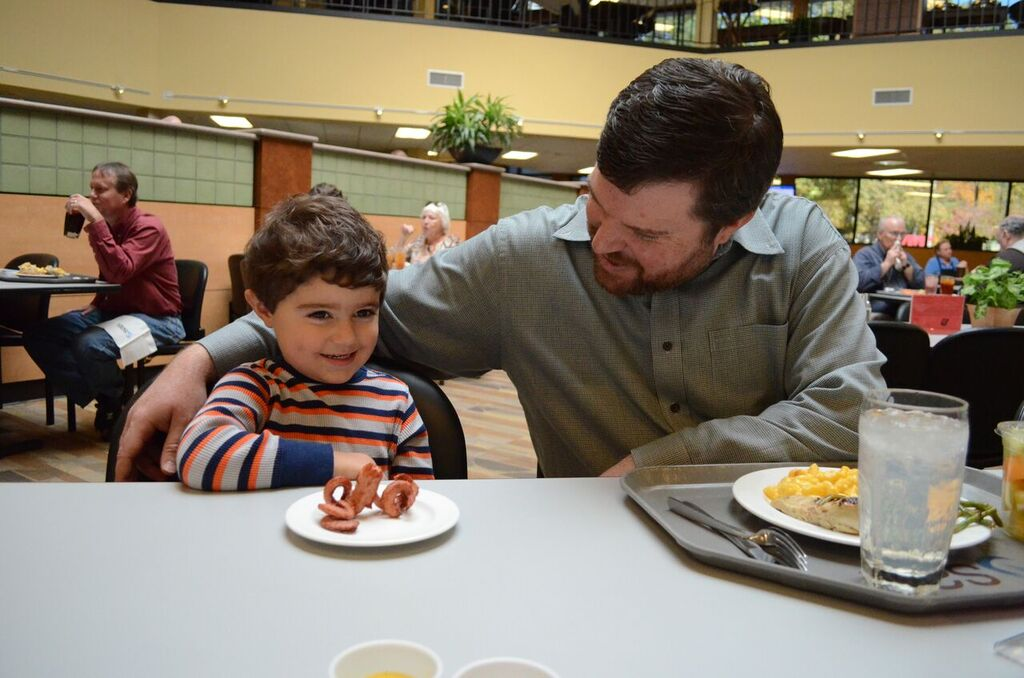 A father and son on-site at one of SAS Institute's campus cafes, which offers child-friendly menus, including octopus-shaped hot dogs.