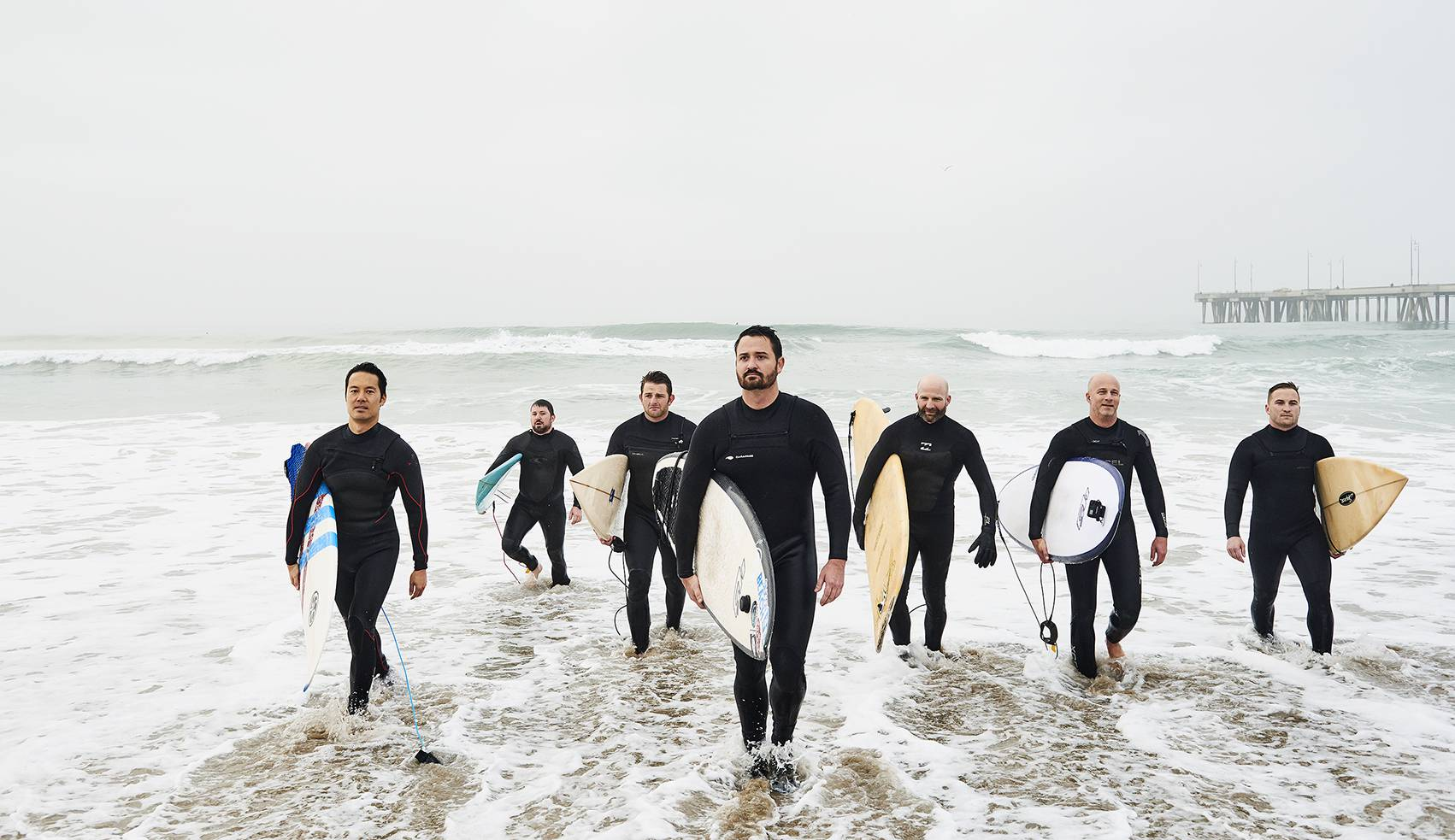 Founder Rob Lambert, center, with a dawn squad of surf-happy tech professionals after a prework session near the Venice Beach pier.