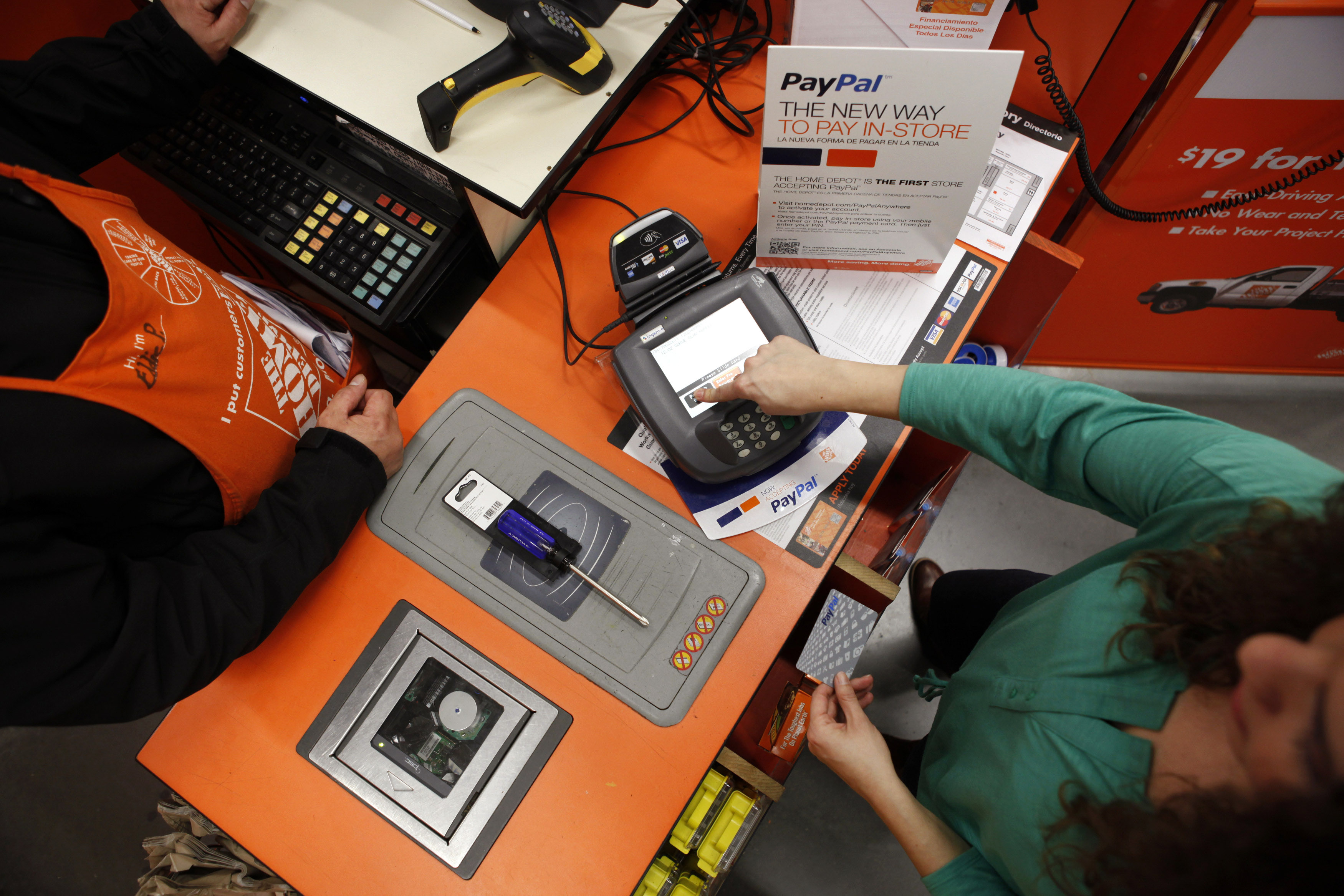 A Home Depot employee and a public relations representative demonstrate how the PayPal card works at a cashier station at a Home Depot store in Daly City
