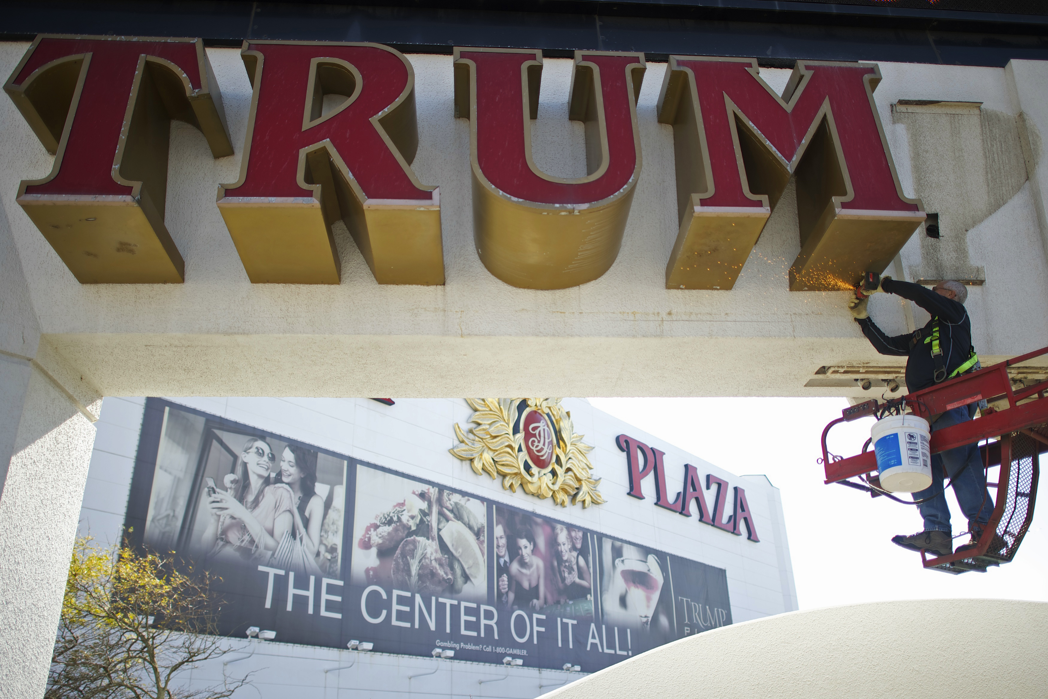 Williams, of Calvi Electric, saws mounts off the letter 'M' from the signage of Trump Plaza Casino in Atlantic City, New Jersey