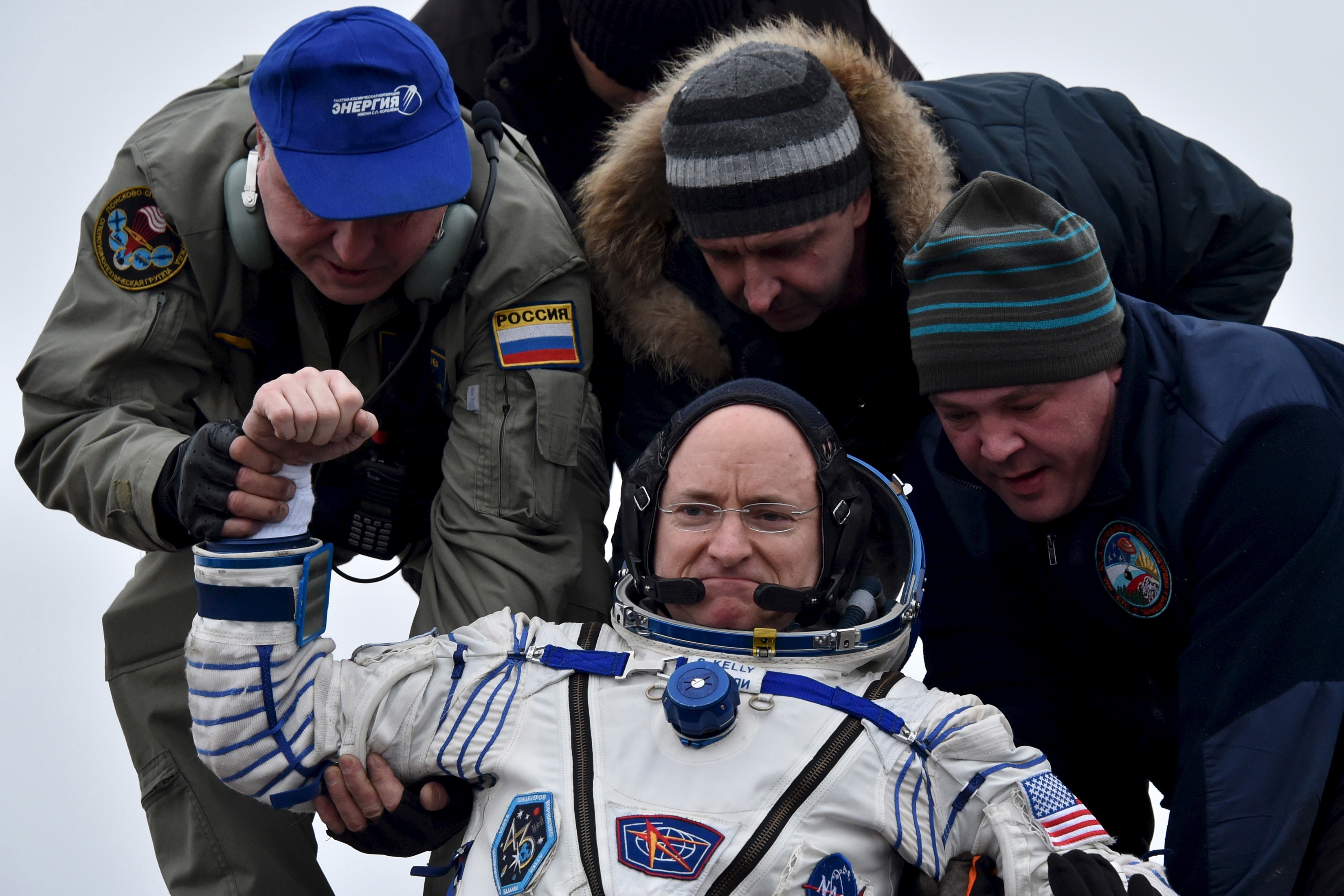 Ground personnel help U.S. astronaut Scott Kelly to get out of a Soyuz capsule shortly after landing near the town of Dzhezkazgan