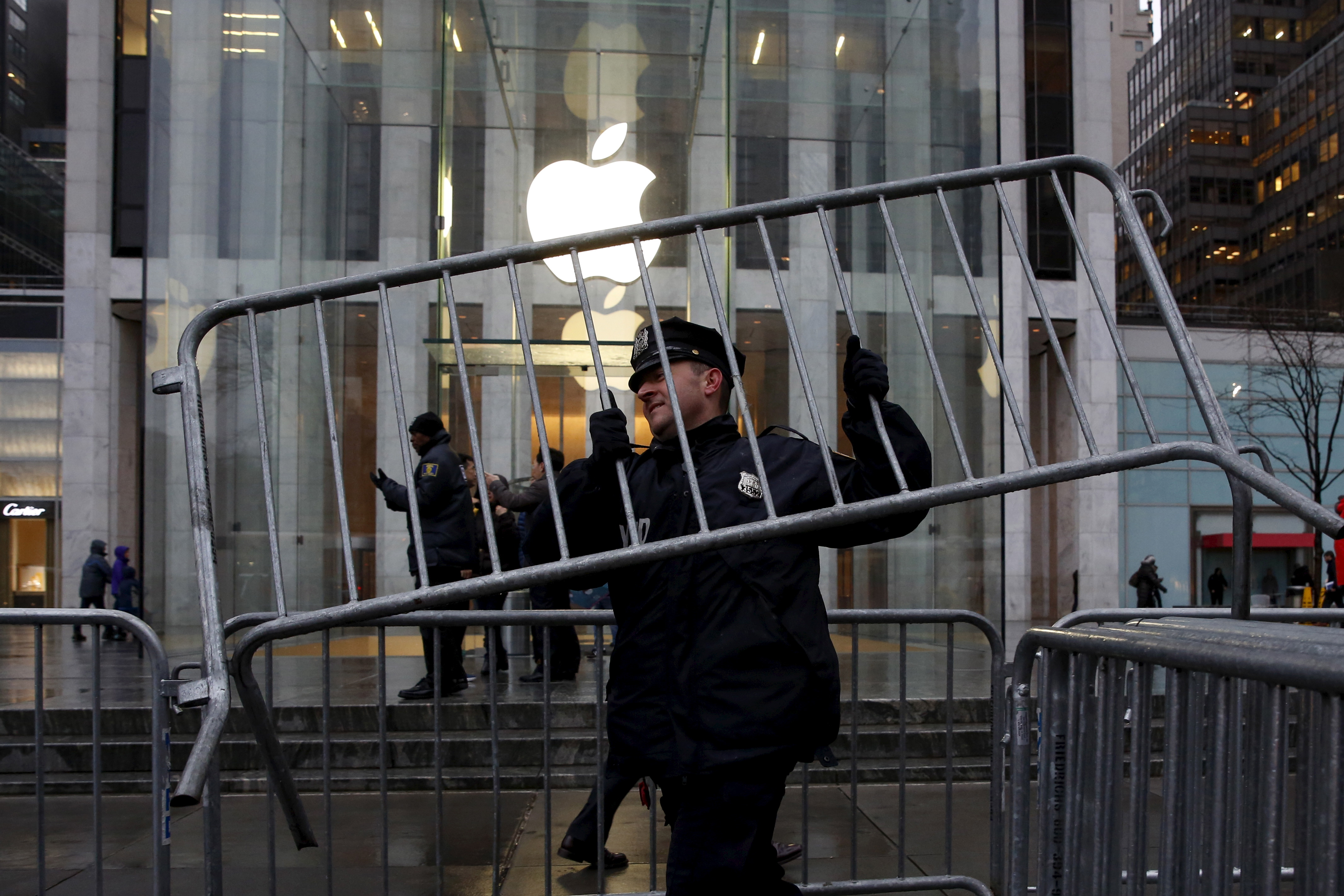 A NYPD officer carries a barrier outside the Apple Store in New York