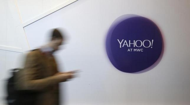 A man walks past a Yahoo logo during the Mobile World Congress in Barcelona