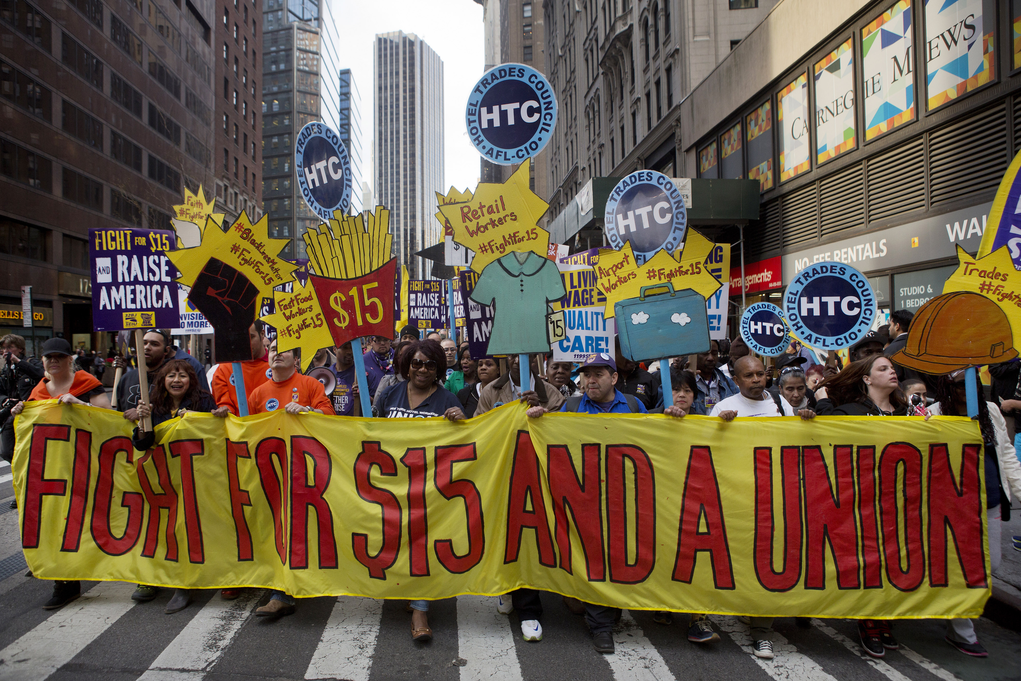 Protesters hold signs at a rally in support of minimum wage increase in New York, U.S., on Wednesday, April 15, 2015. Fast-food workers held rallies in 236 U.S. cities Wednesday in their biggest protest yet for higher pay and union rights. Photographer: Victor J. Blue/Bloomberg